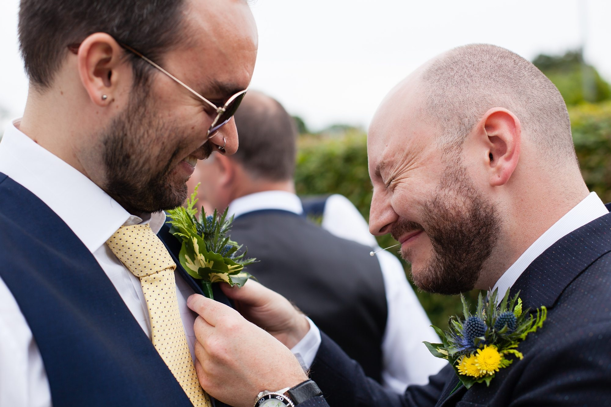 groom with pin in mouth at York Barn wedding with groomsman with sunglasses