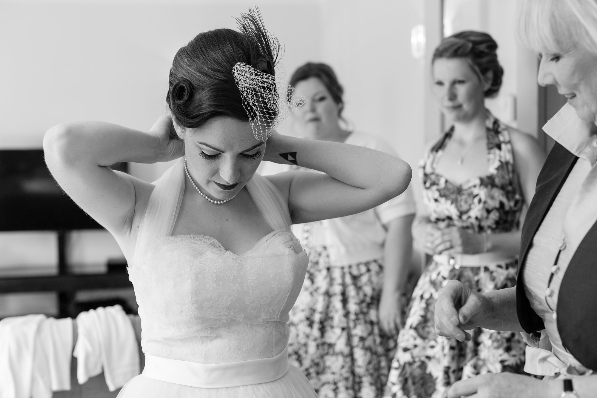 black and white picture of bride messing with hair with guests
