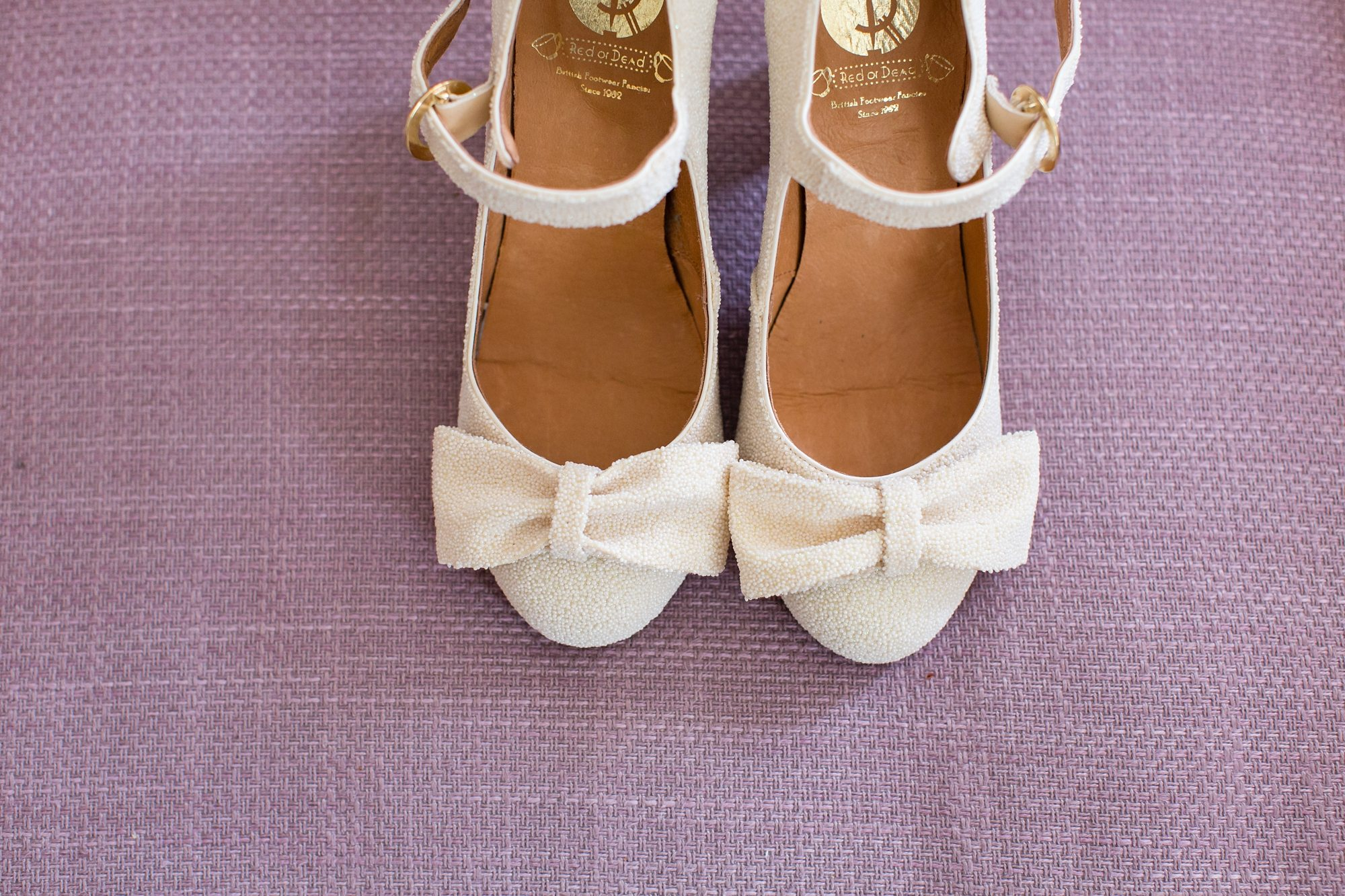 white womens shoes with bows on pink background