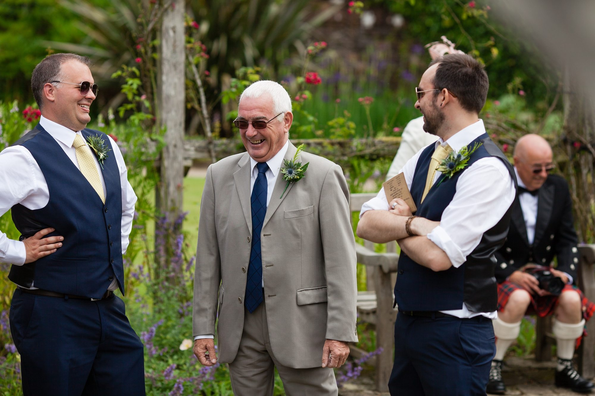 wedding guests wearing sunglasses with kilt and flowers