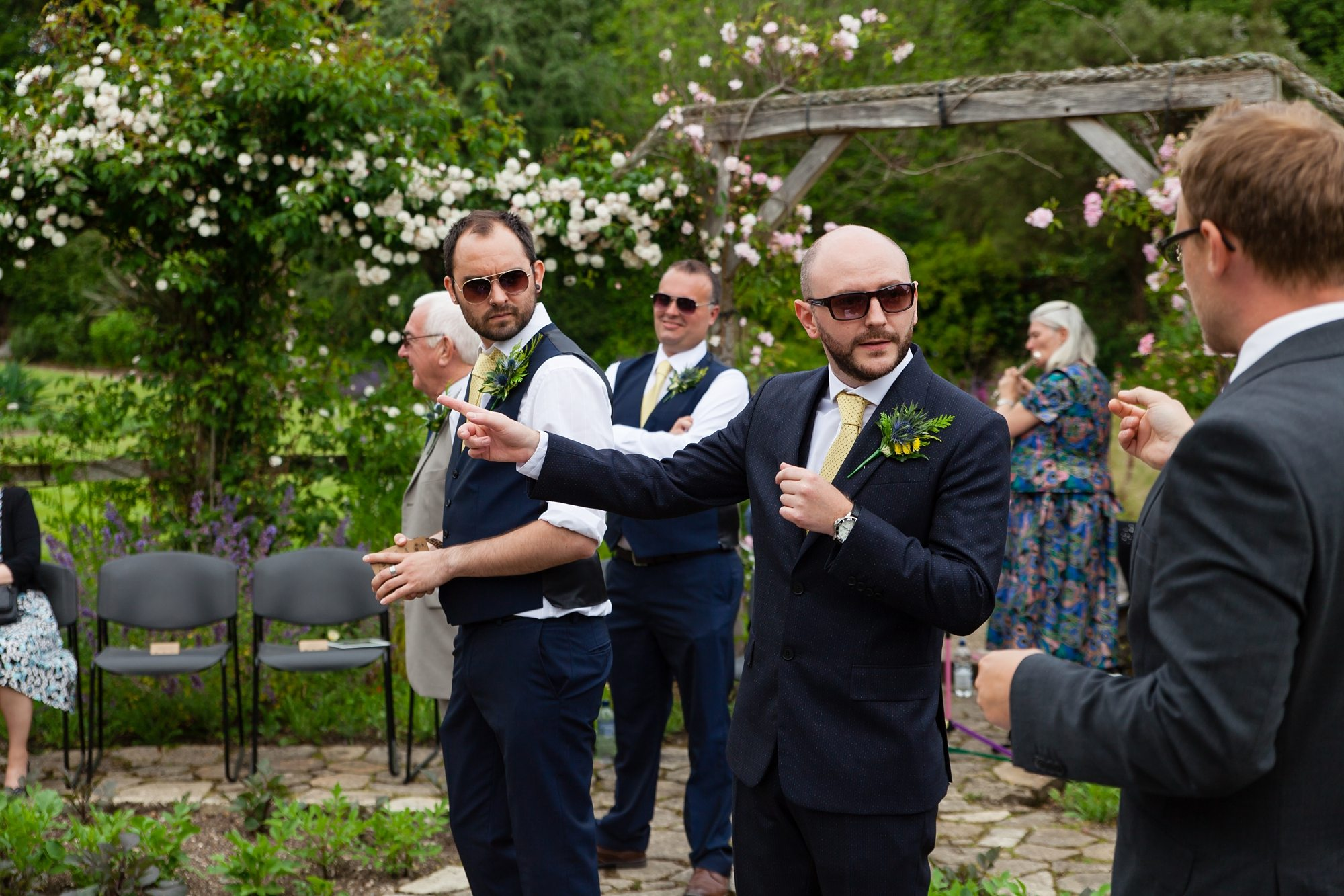 groom with sunglasses pointing under archway outside
