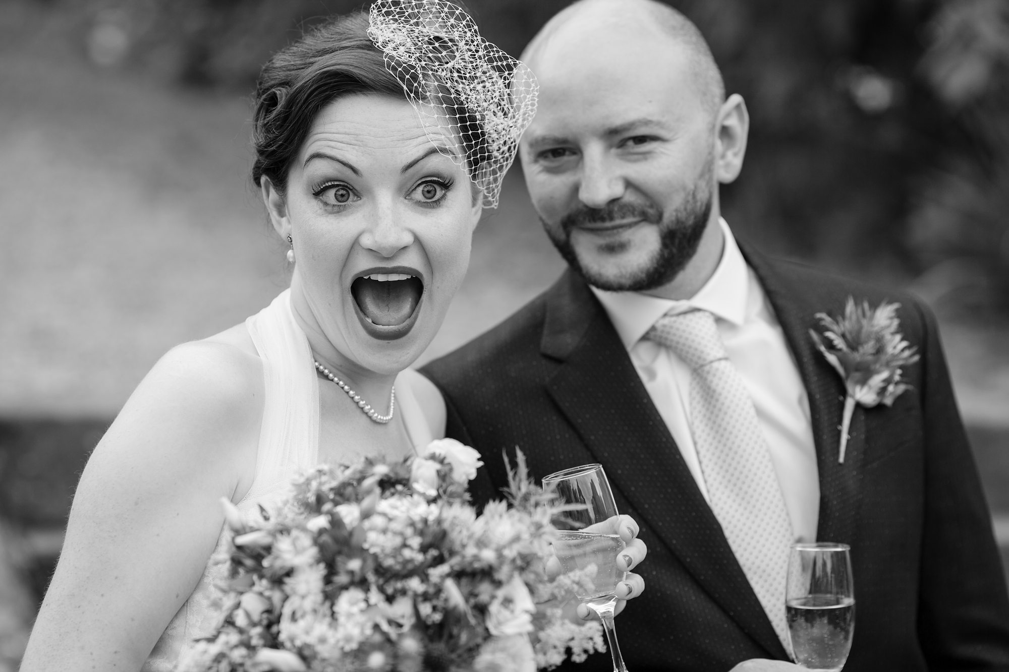 groom smiling and bride pulling funny face holding boque at York wedding