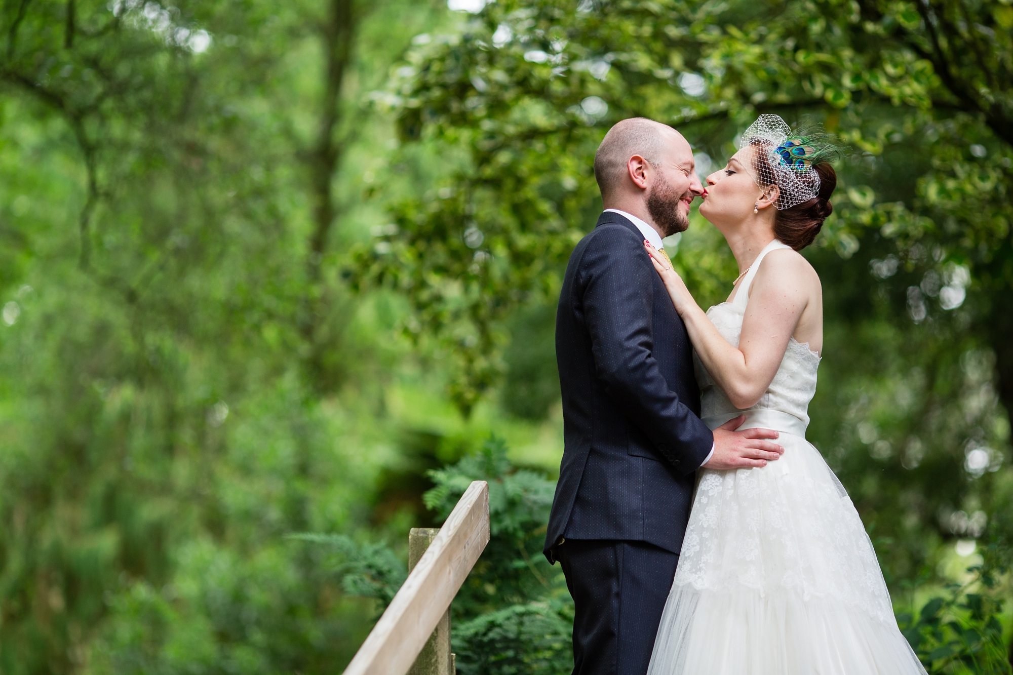 bride and groom couple kissing hugging under trees