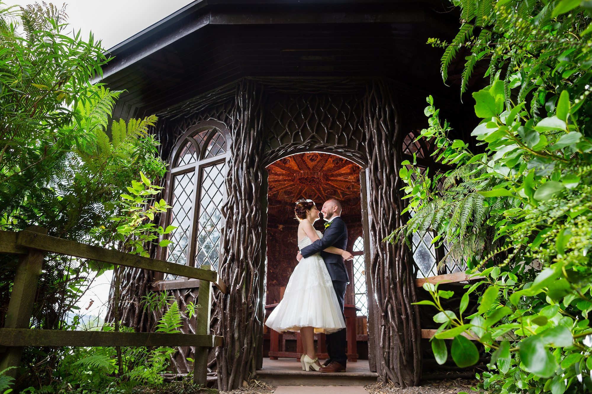 redhead bride kissing groom and hugging under wooden archway door