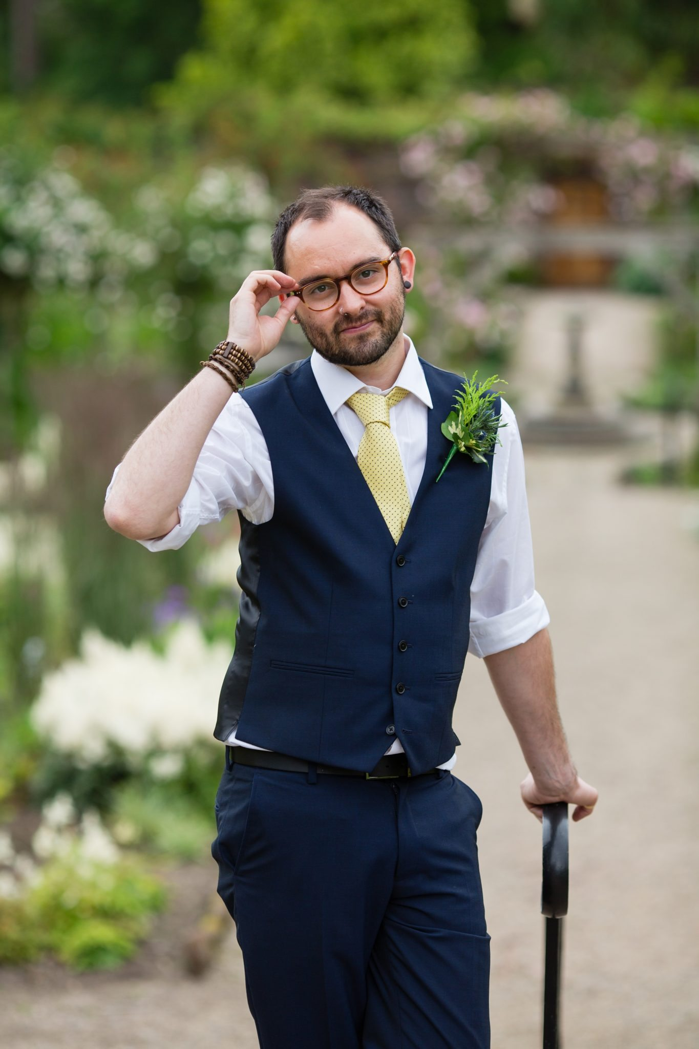 wedding guest with glasses looking at camera and leaning on cane