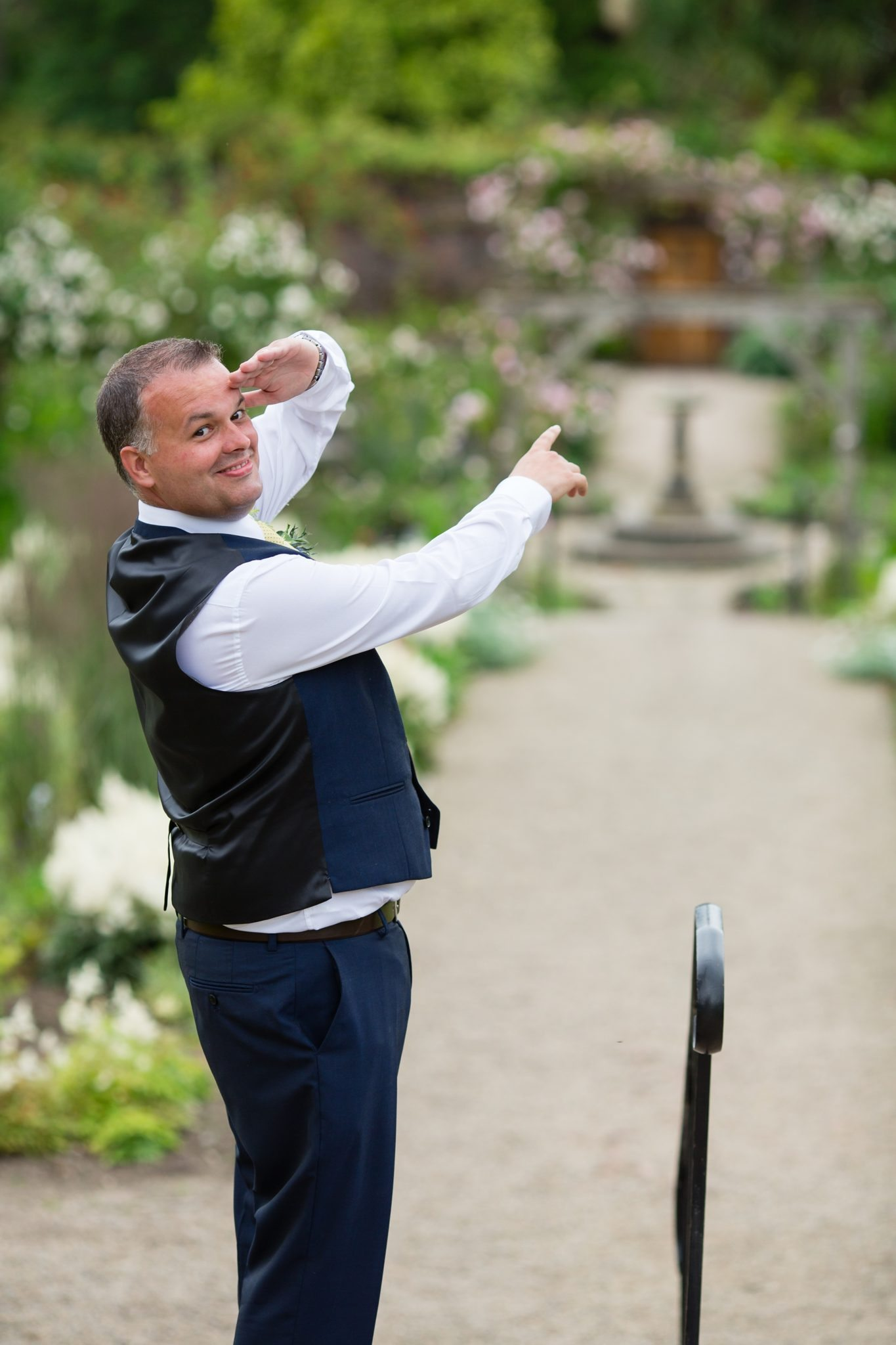 wedding guest pointing off camera and looking at camera with cane