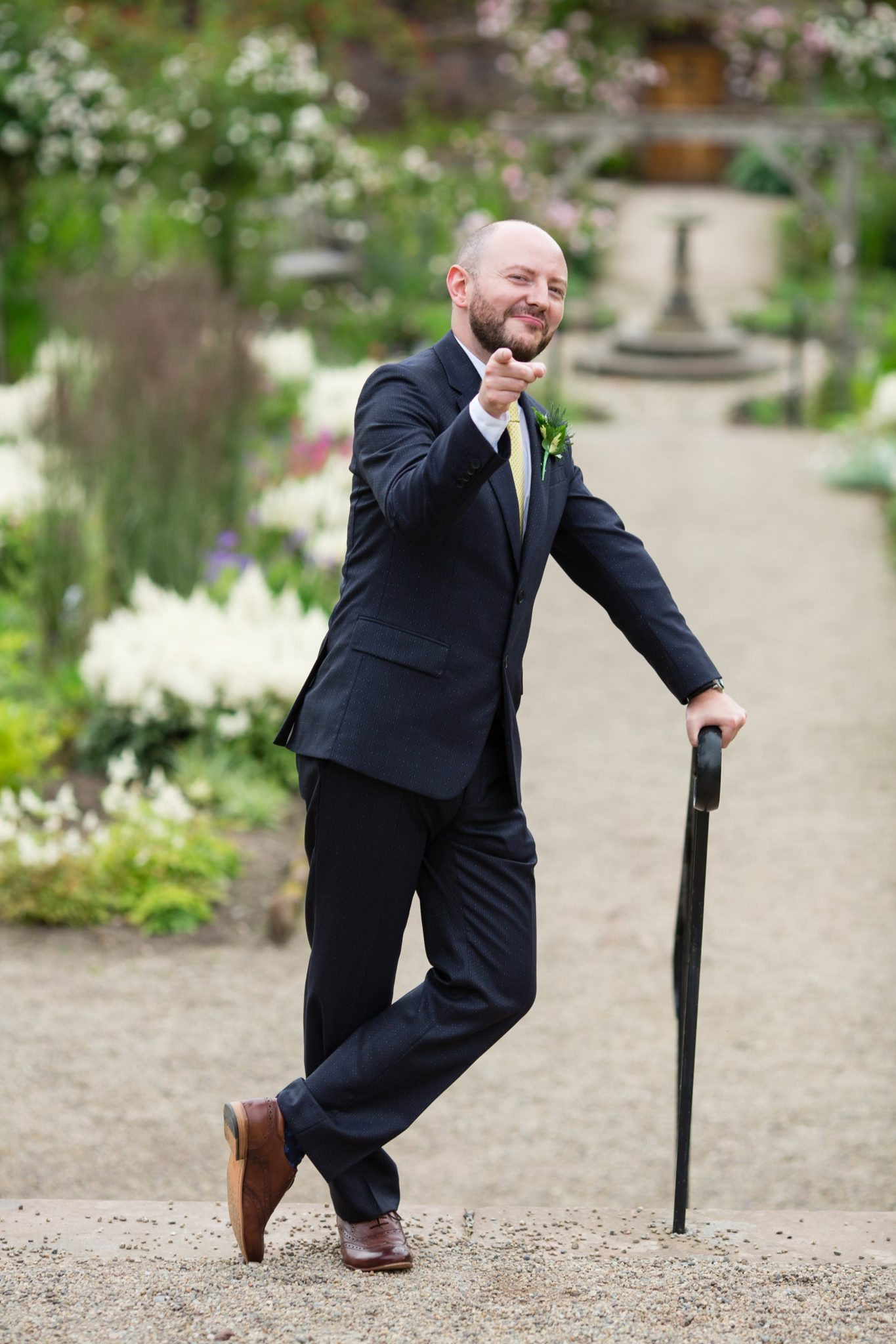 groom pointing at camera holding and leaning on cane
