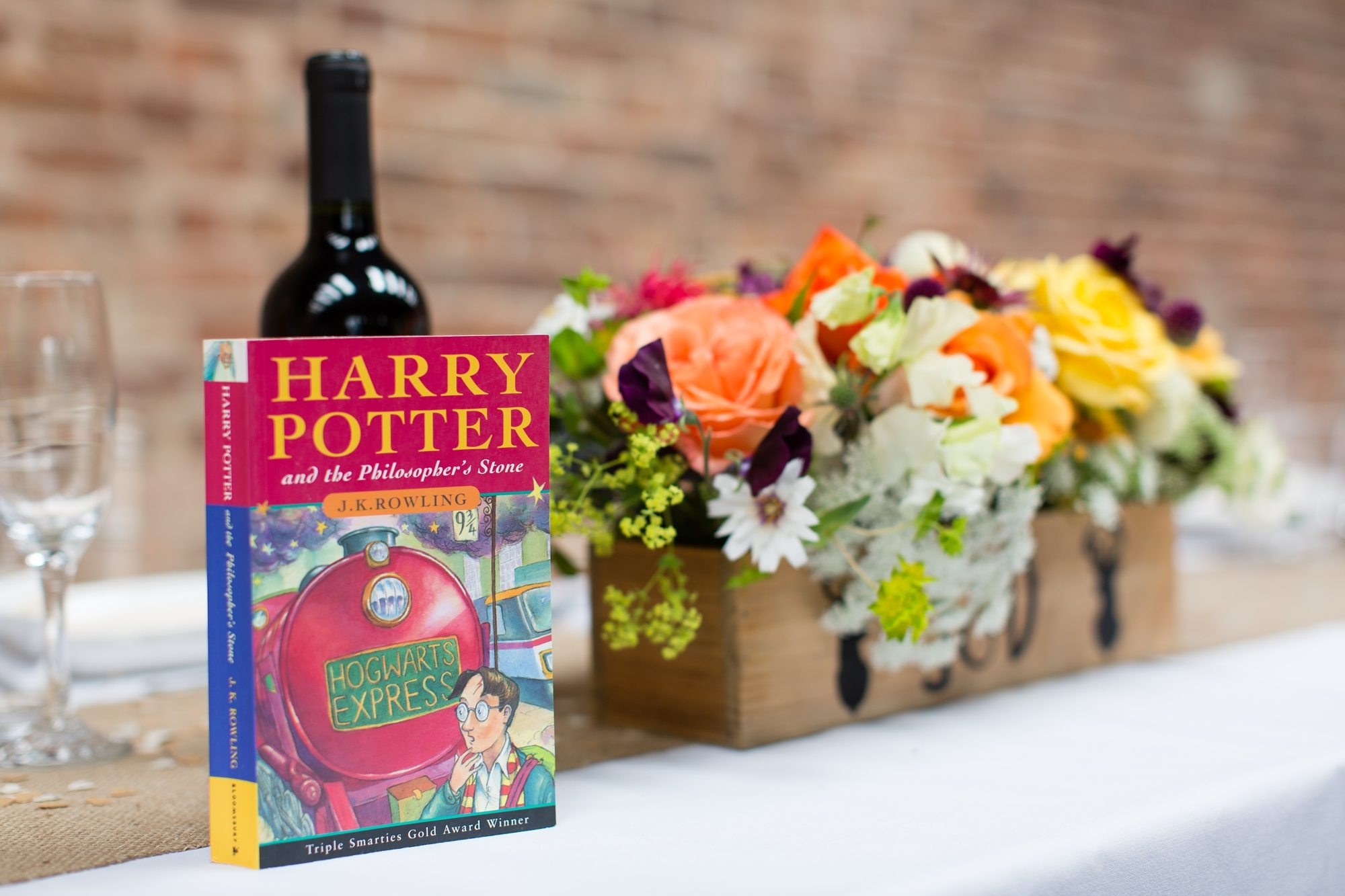 Harry Potter and the philosopher's stone book next to winde bottle and flowers