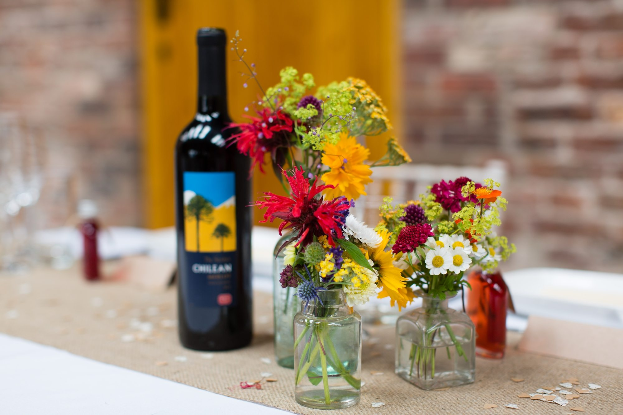 flowers in glass vases next to wine glass