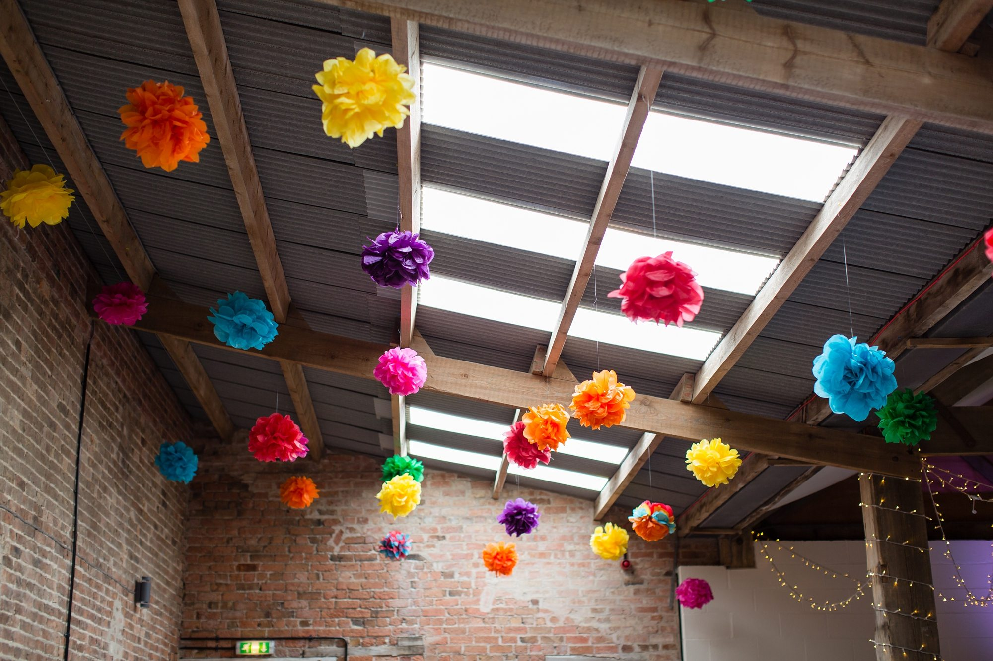 hanging flowers under skylight in wedding barn