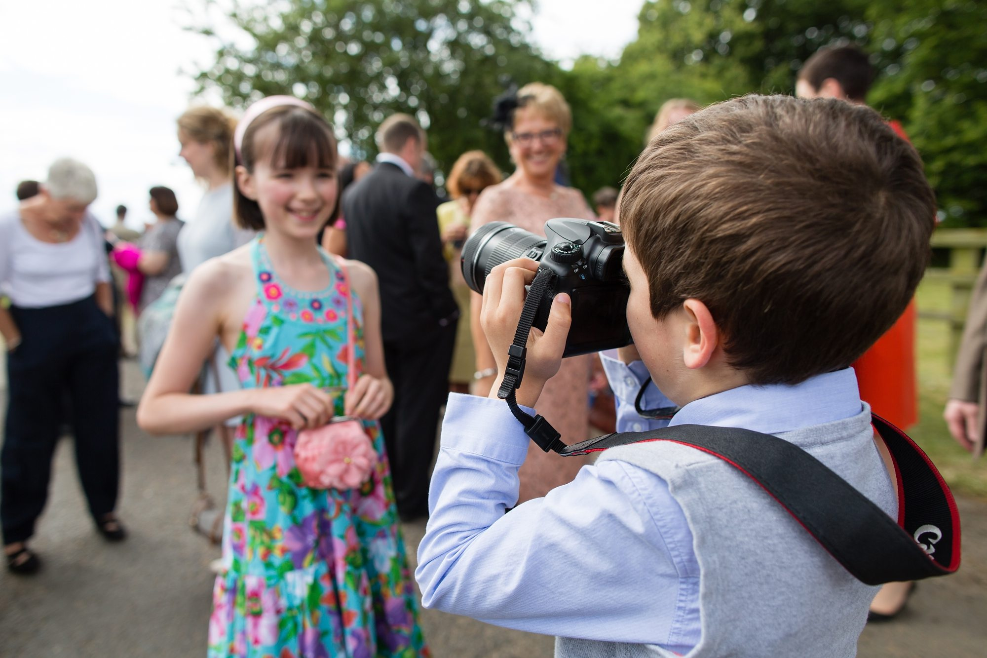 little boy holding camera and taking picture of little girl