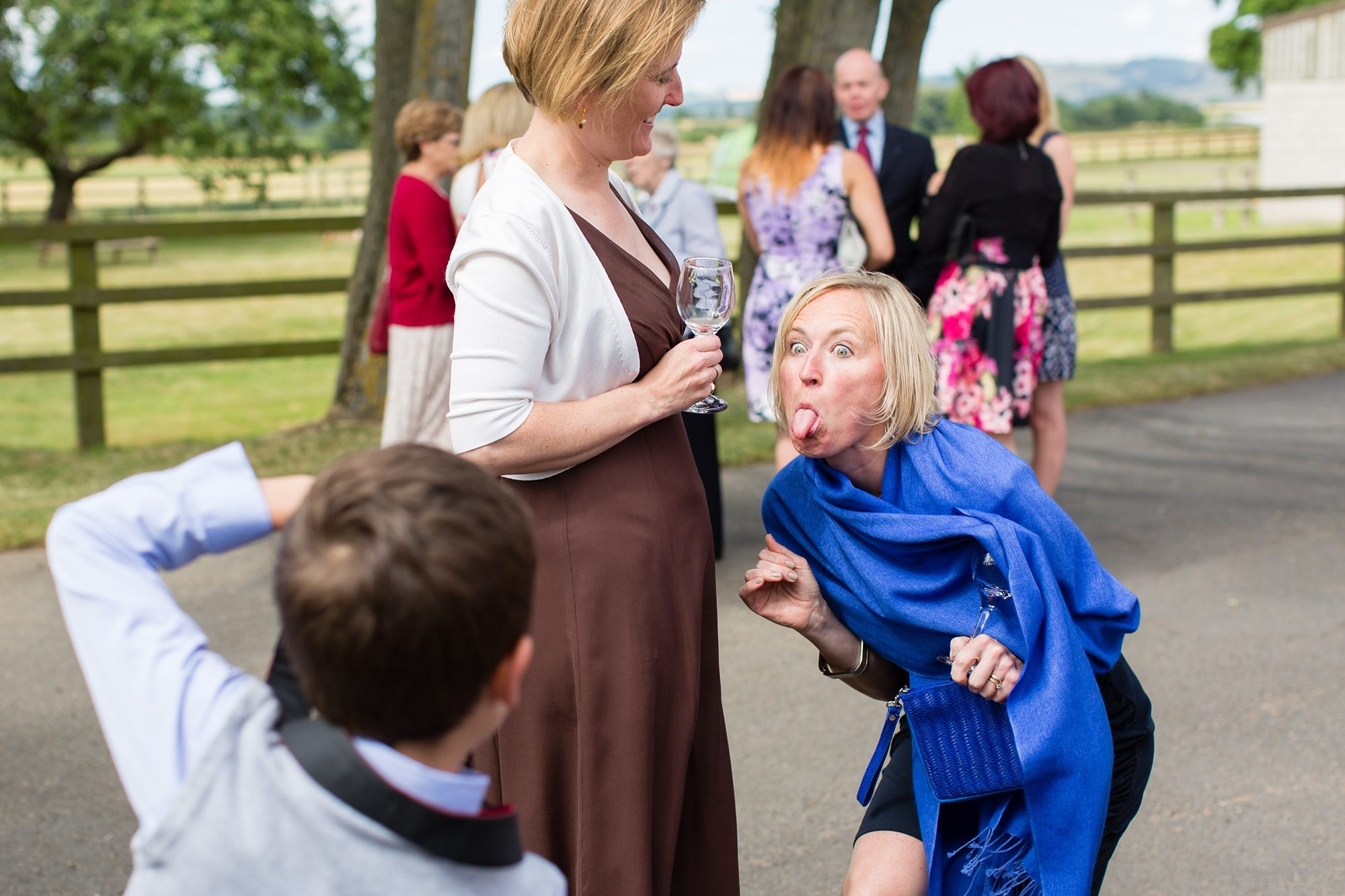 wedding guest pulling silly face and sticking tongue out