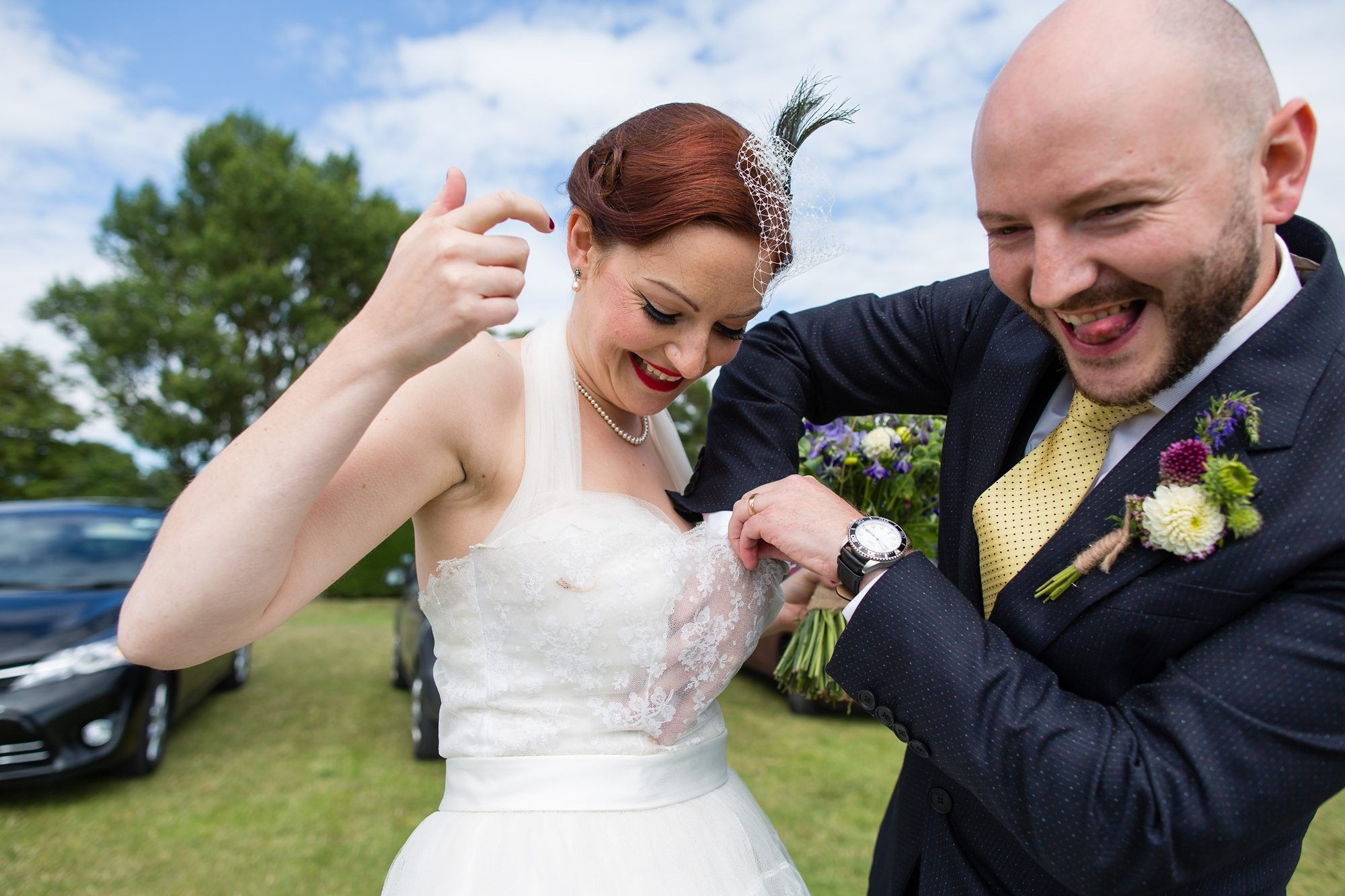 groom pulling face while grabbing something in redhead bride's dress