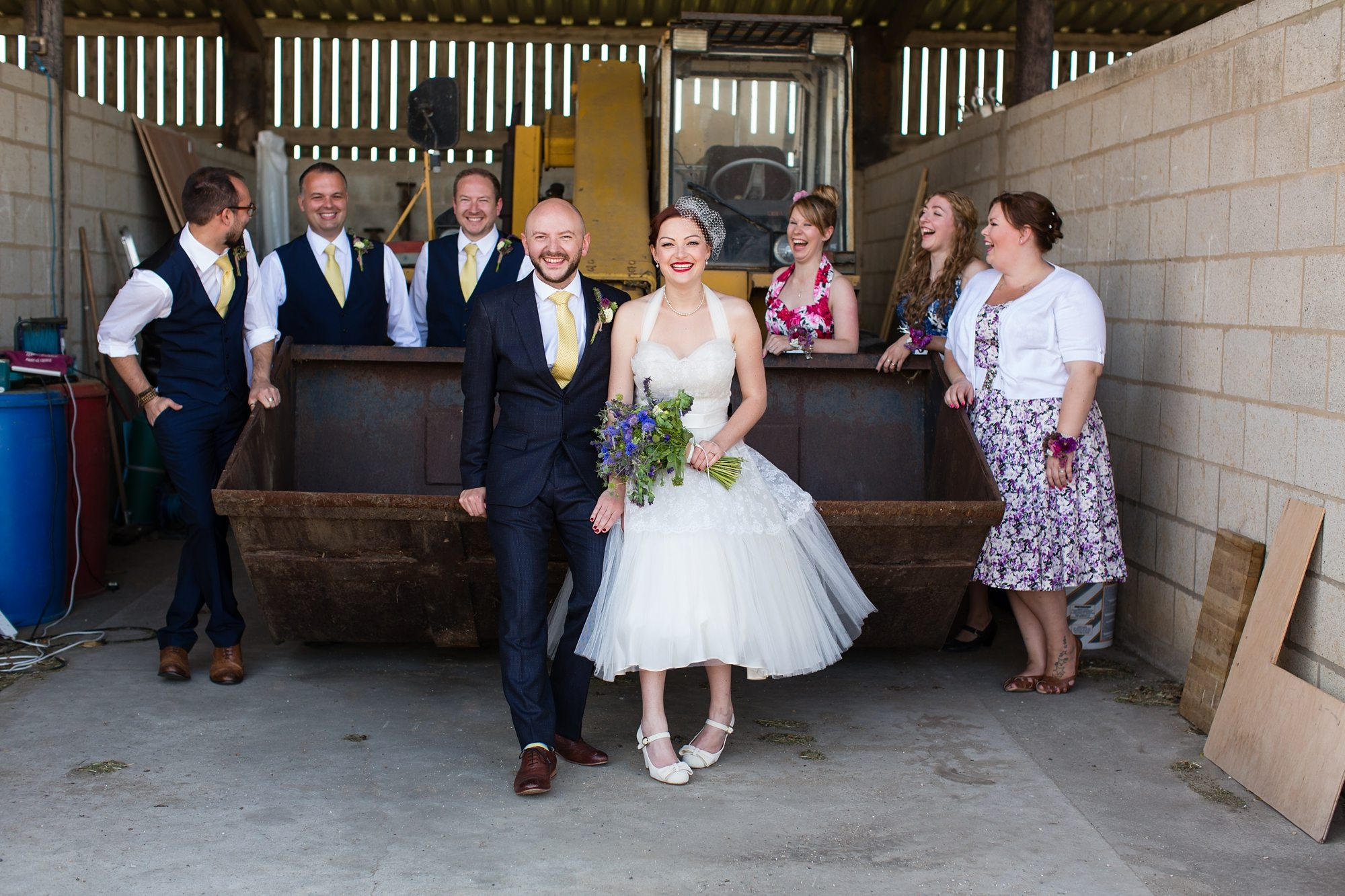 bride and groom holding hands and bouque under barn with wedding guests
