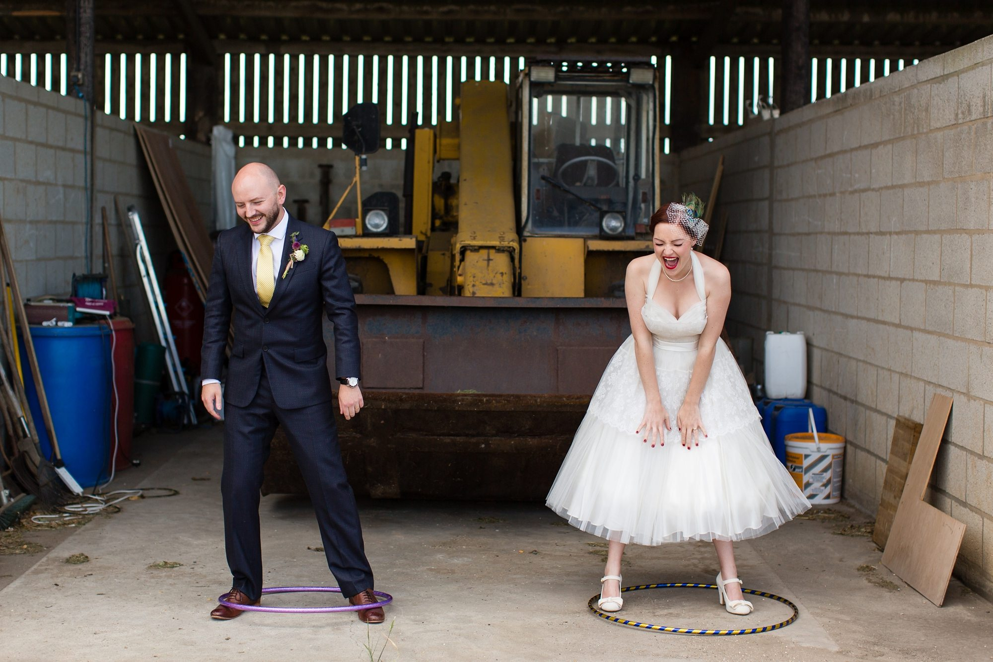 groom and bride lauging with hula hoops under their feet