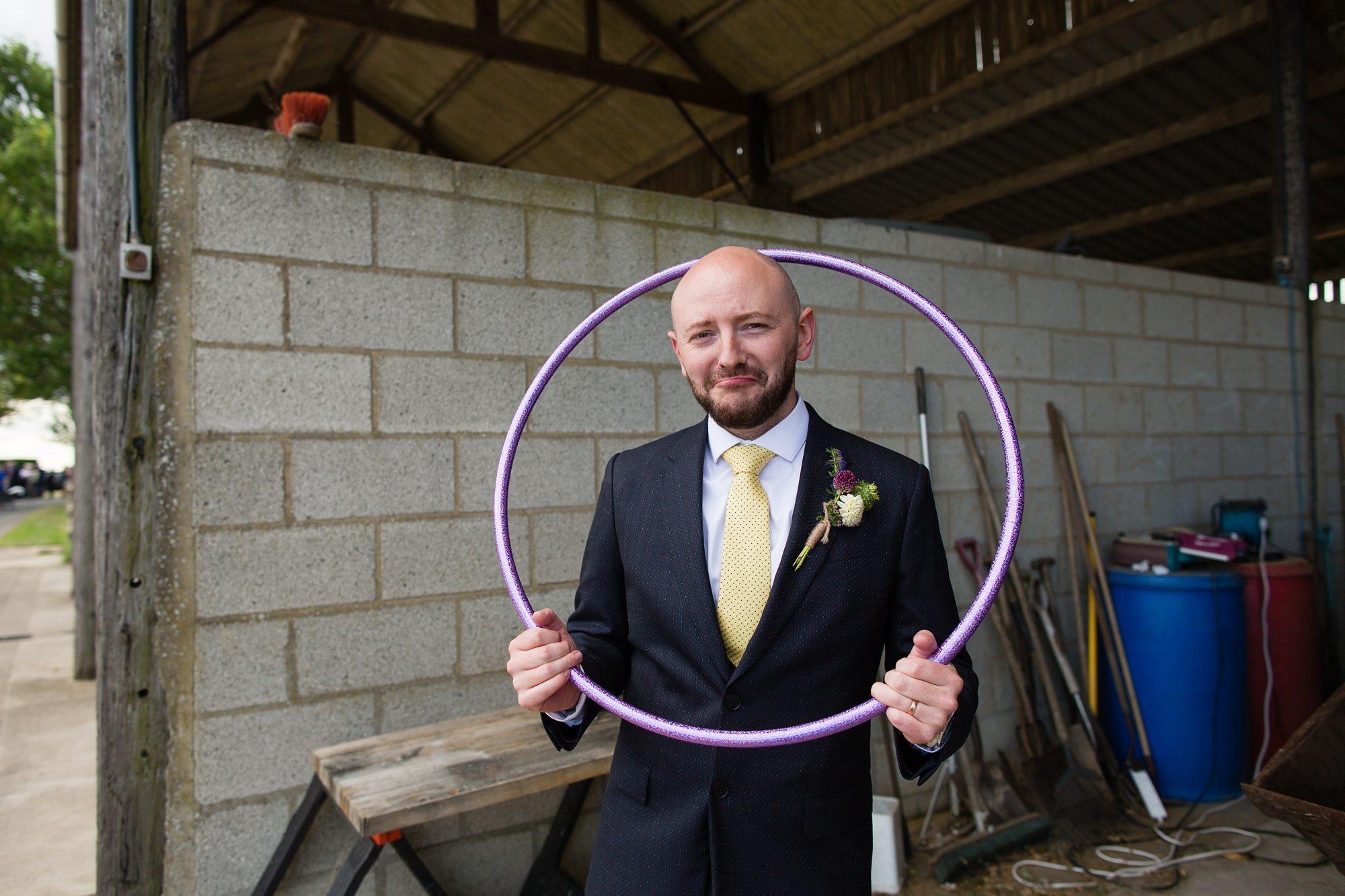 groom pulling sad face holding hula hoop