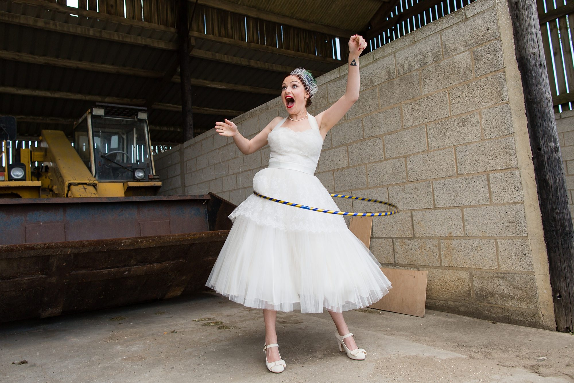 bride pulling face while hula hooping with concrete wall behind
