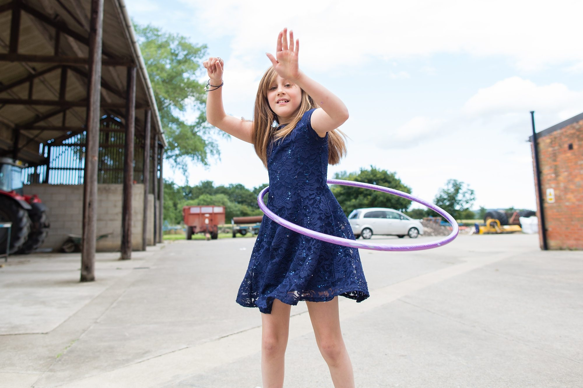 little girl wedding guest hula hooping in barn in carpark