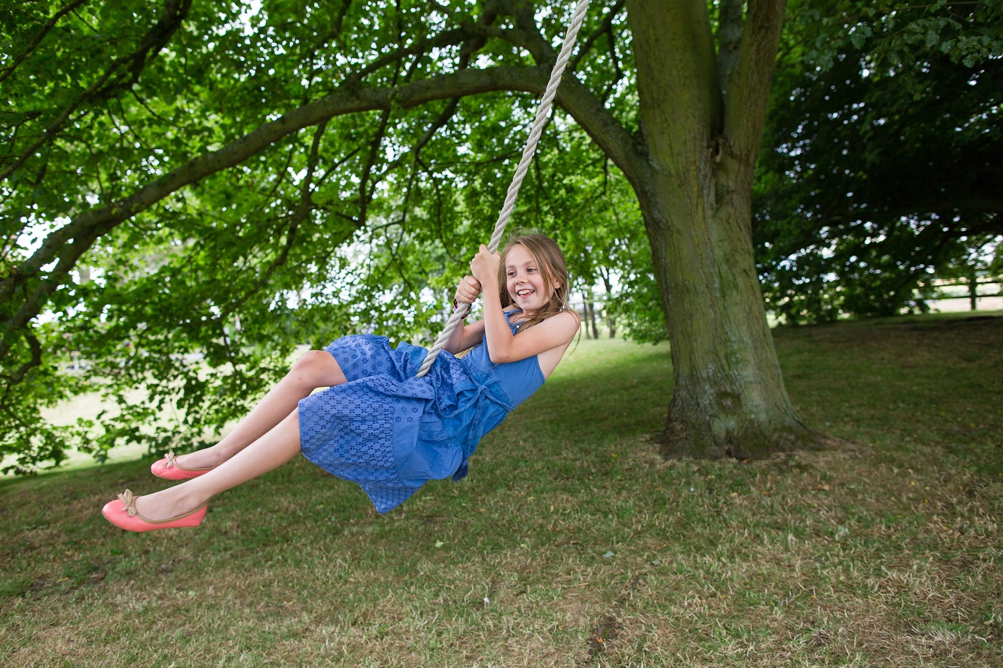 wedding guest little girl swinging on rope swing under tree