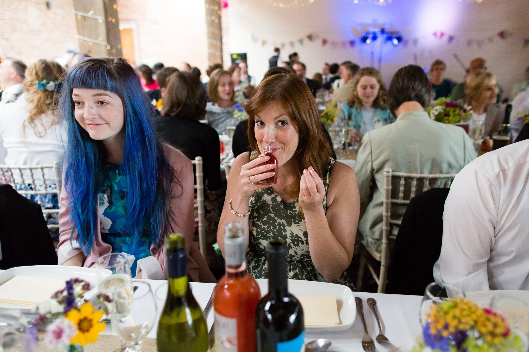 blue haired guest and brunette guest staring at camera smelling in barn wedding