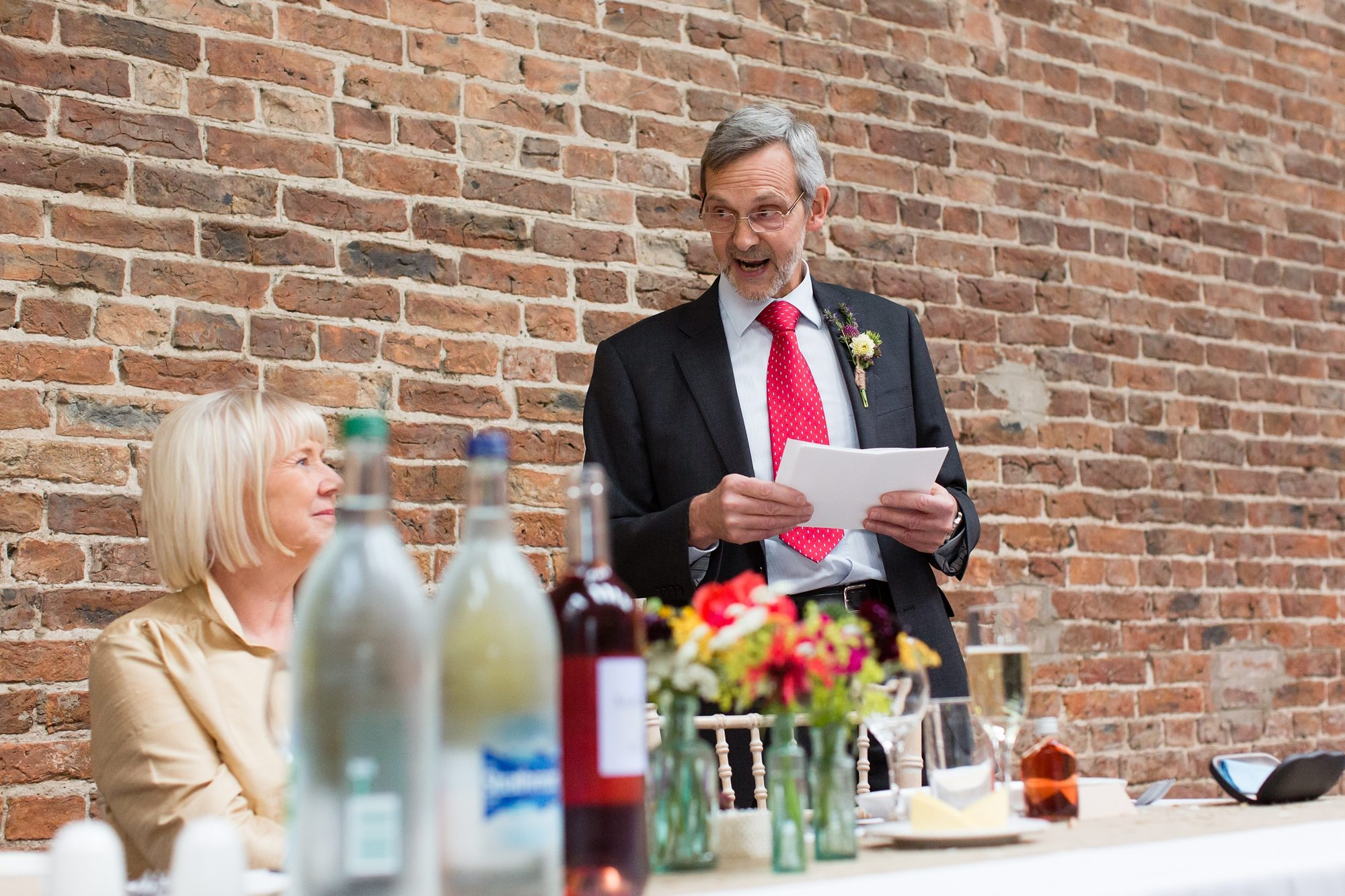 wedding guest giving speach with brick wall backdrop