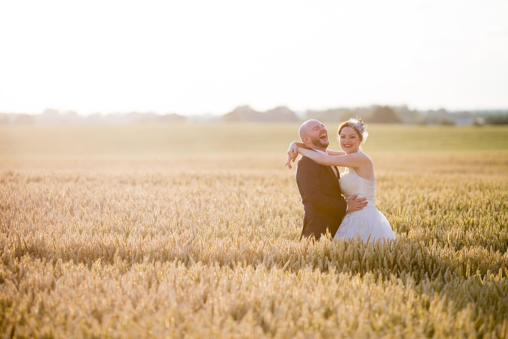 groom hugging holding bride in cronfield under bright sun