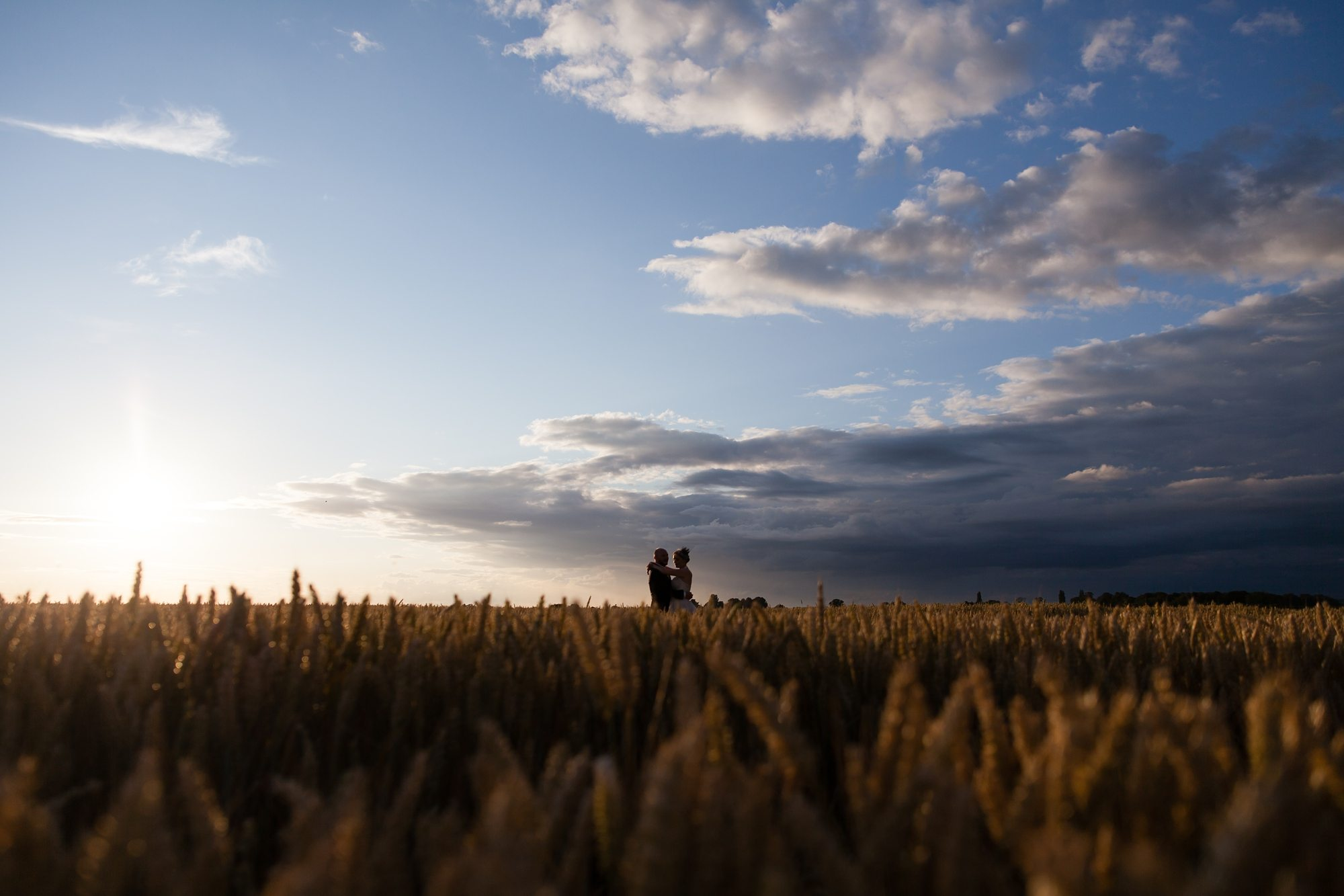 bride and groom hugging in siloet in cornfield under a blue sky
