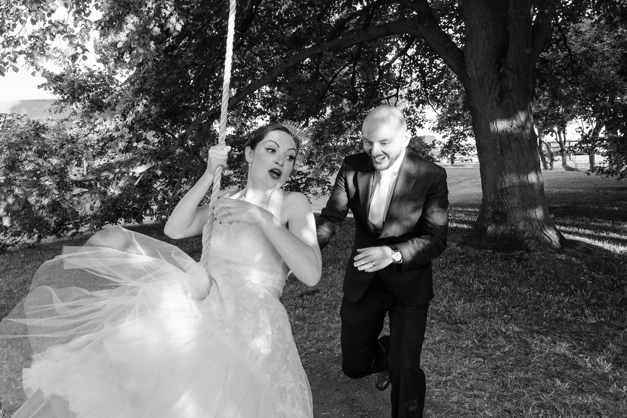groom pushing bride on tire swing under tree