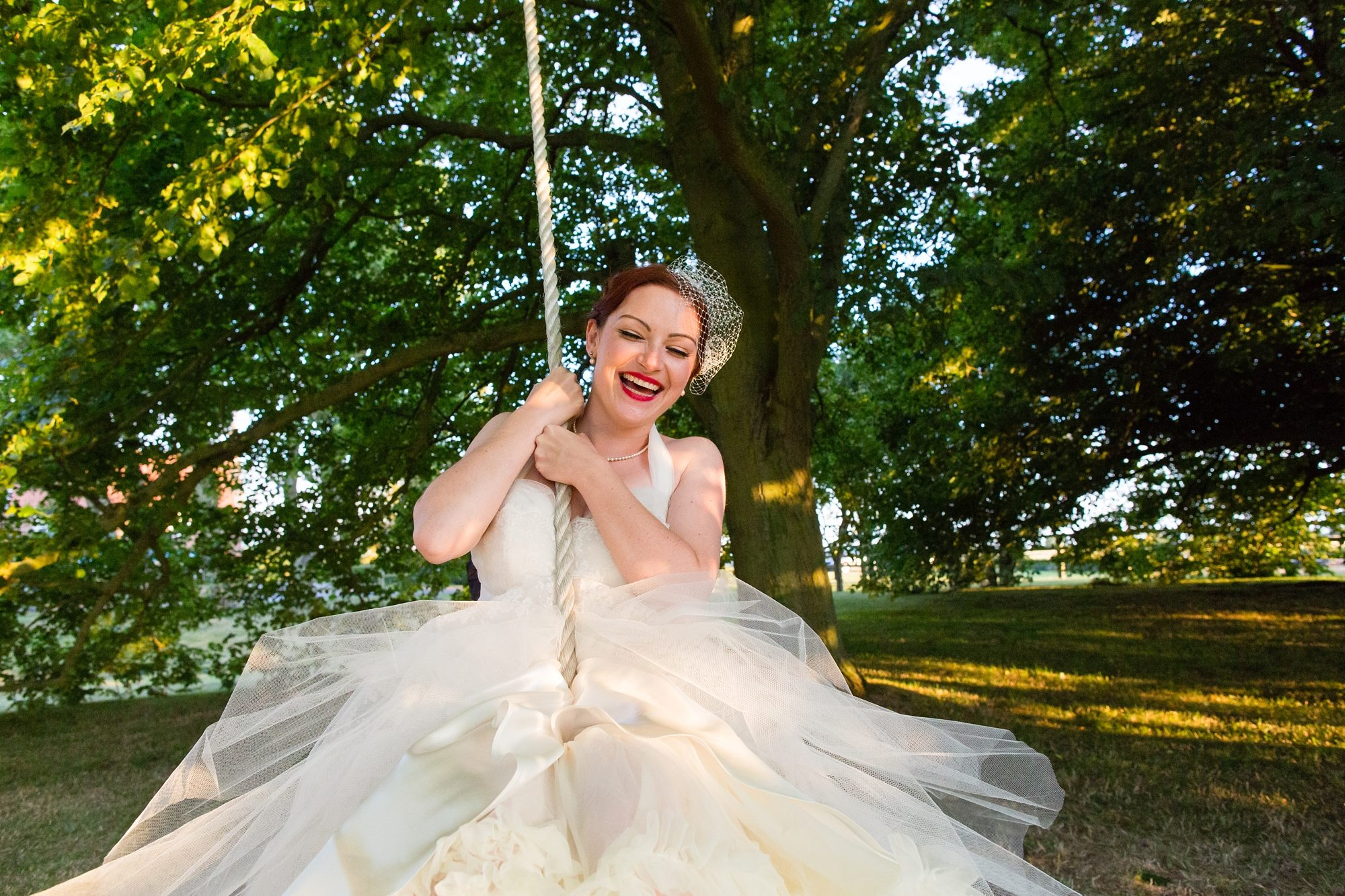 bride swinging on tire swing under tree in York wedding