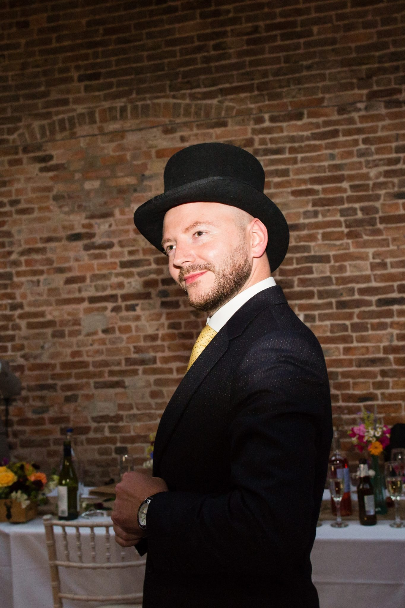 groom with top hat sorting out suit