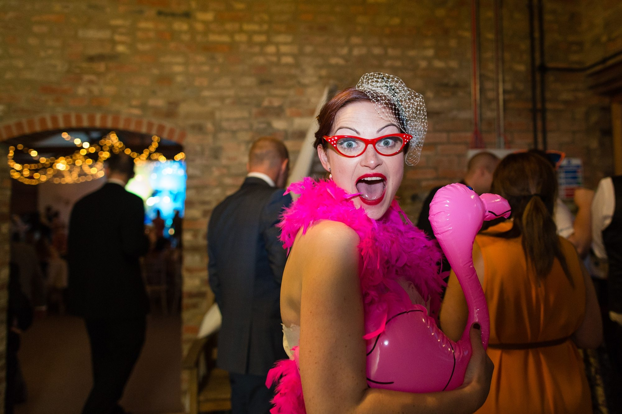 bride looking at camera with inflatable flamingo and silly glasses