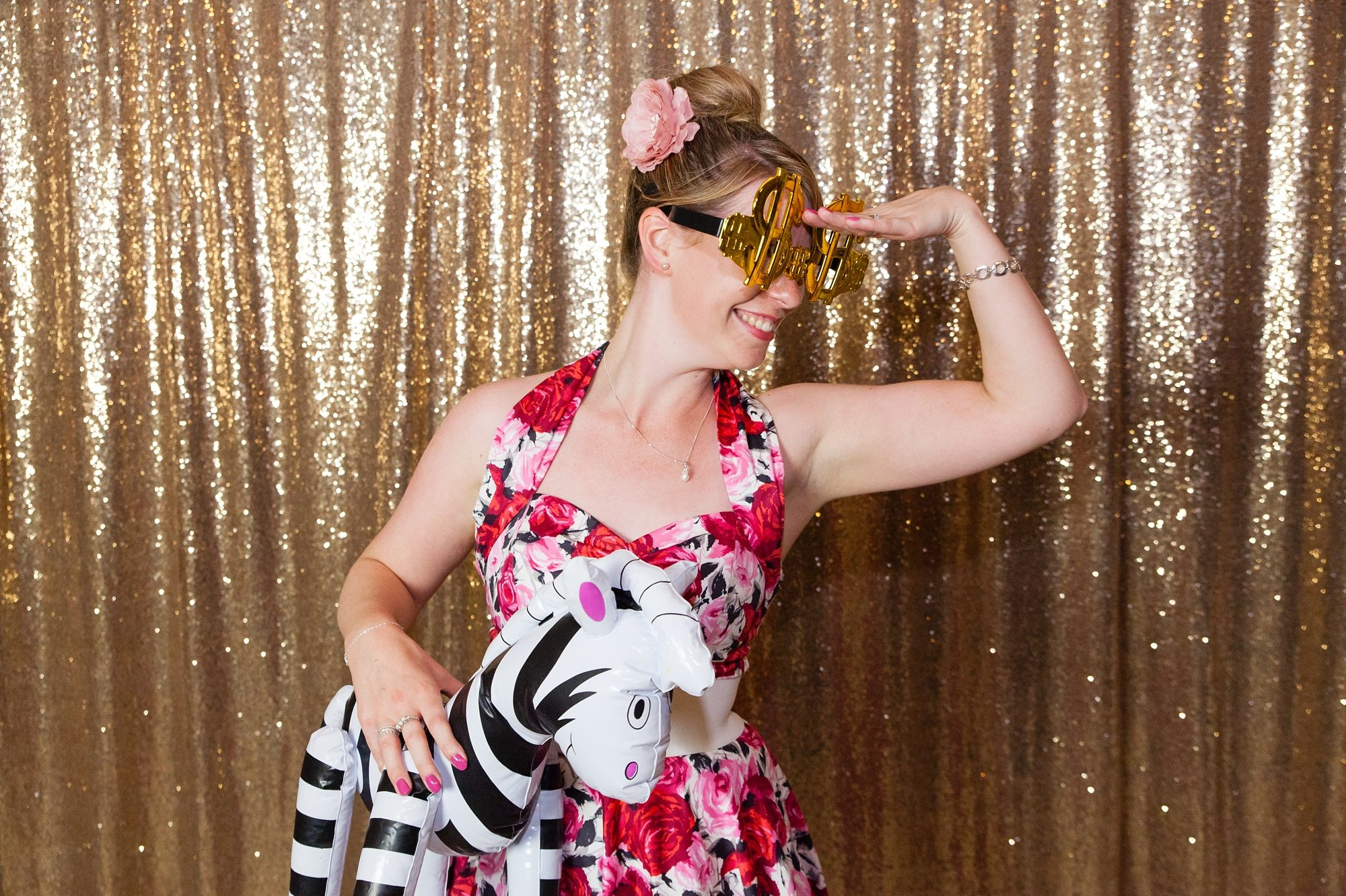 wedding guest wearing floral dress with silly glasses and inflatable zebra