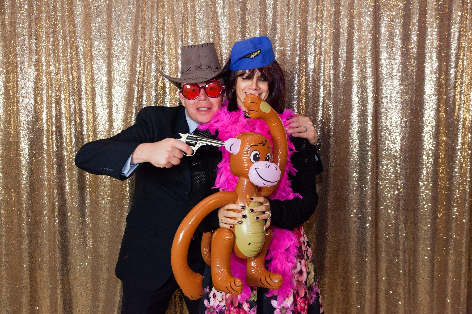 couple with glittery backdrop holding bowa and inflatable monkey with gun