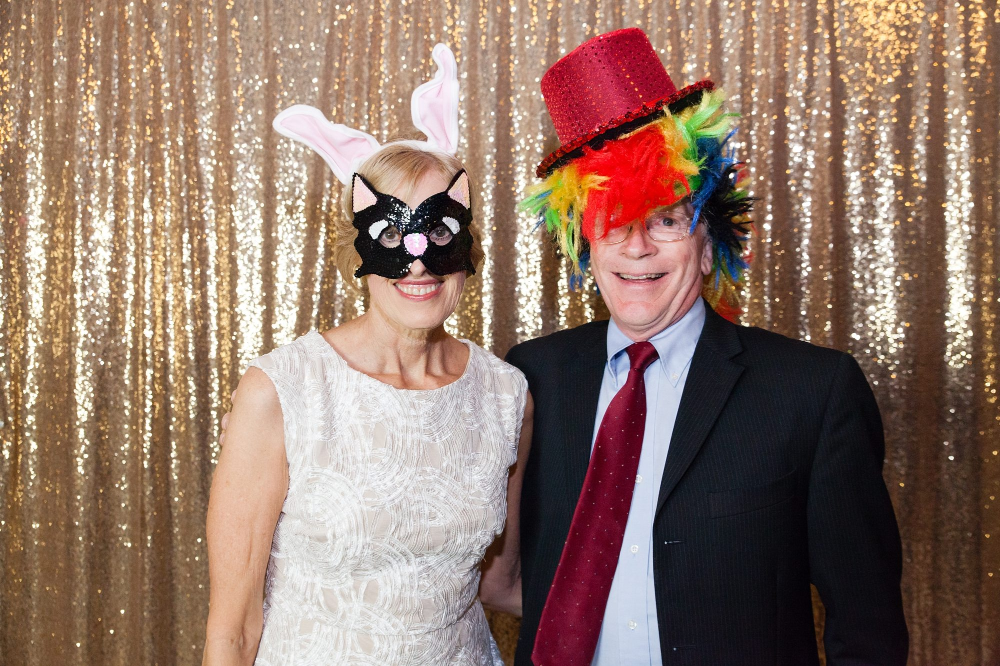old couple wearing silly hat in party outfit photobooth