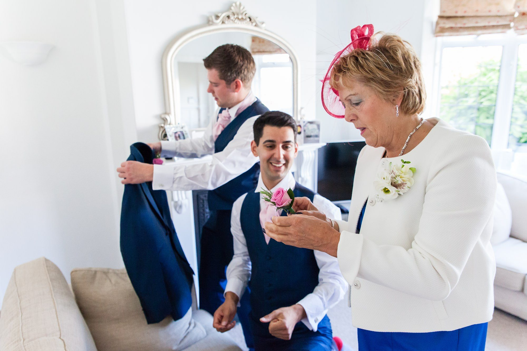 Groom & best man being helped with their buttonholes by groom's mum