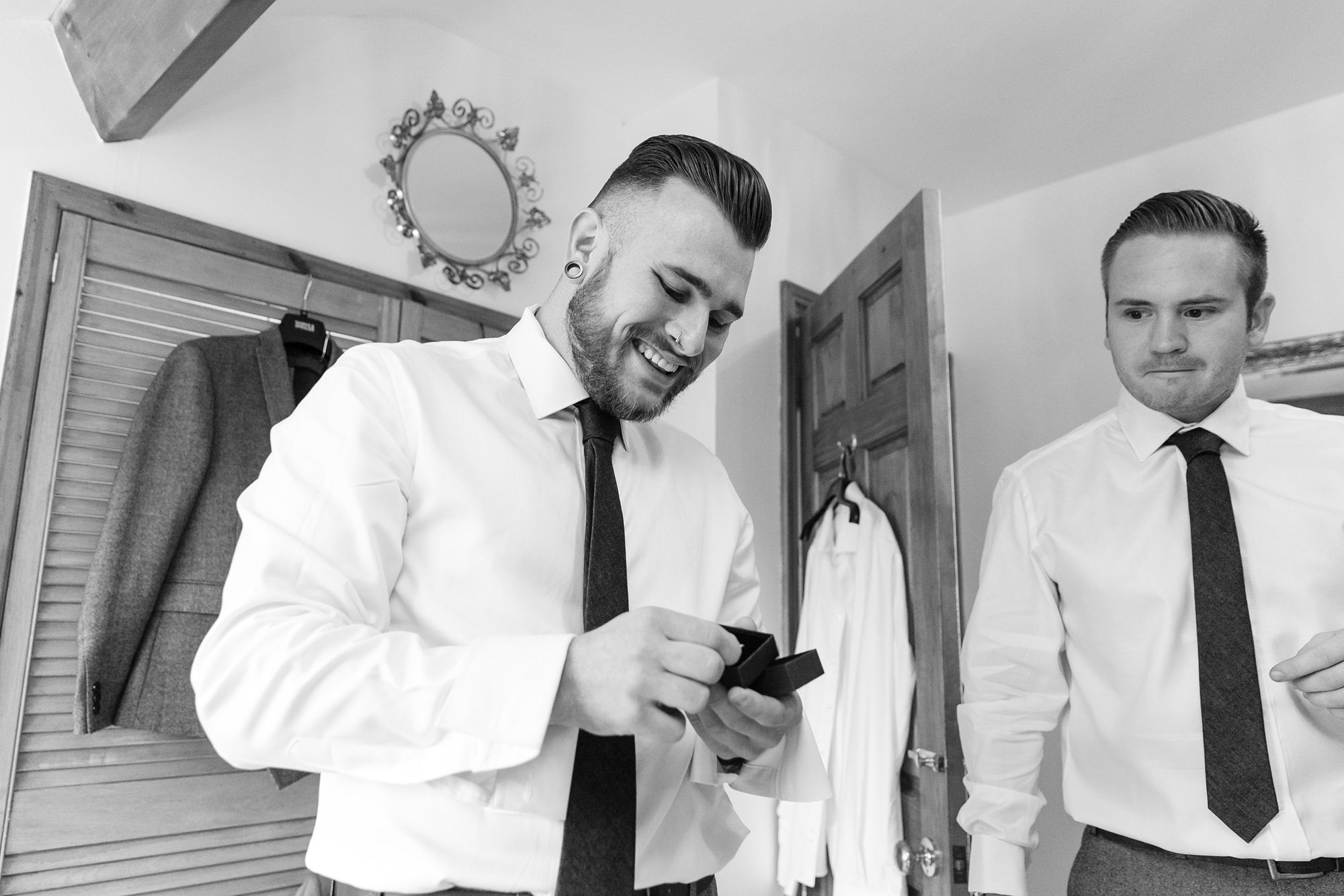 Groom with bald fade hair style smiles as he opens a gift