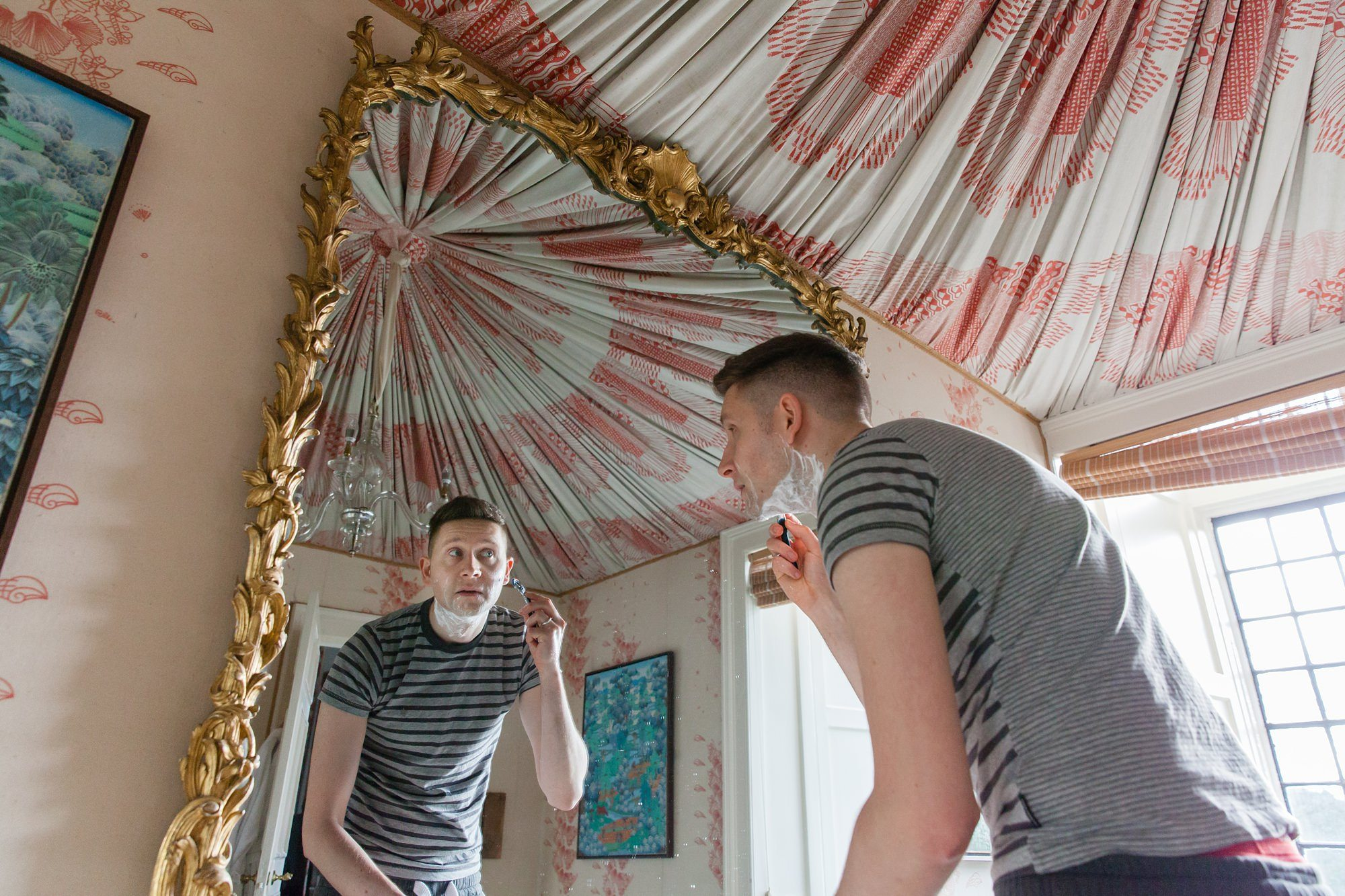 Groom shaving whilst looking into a mirror. French fabric hangs fromt he ceiling.