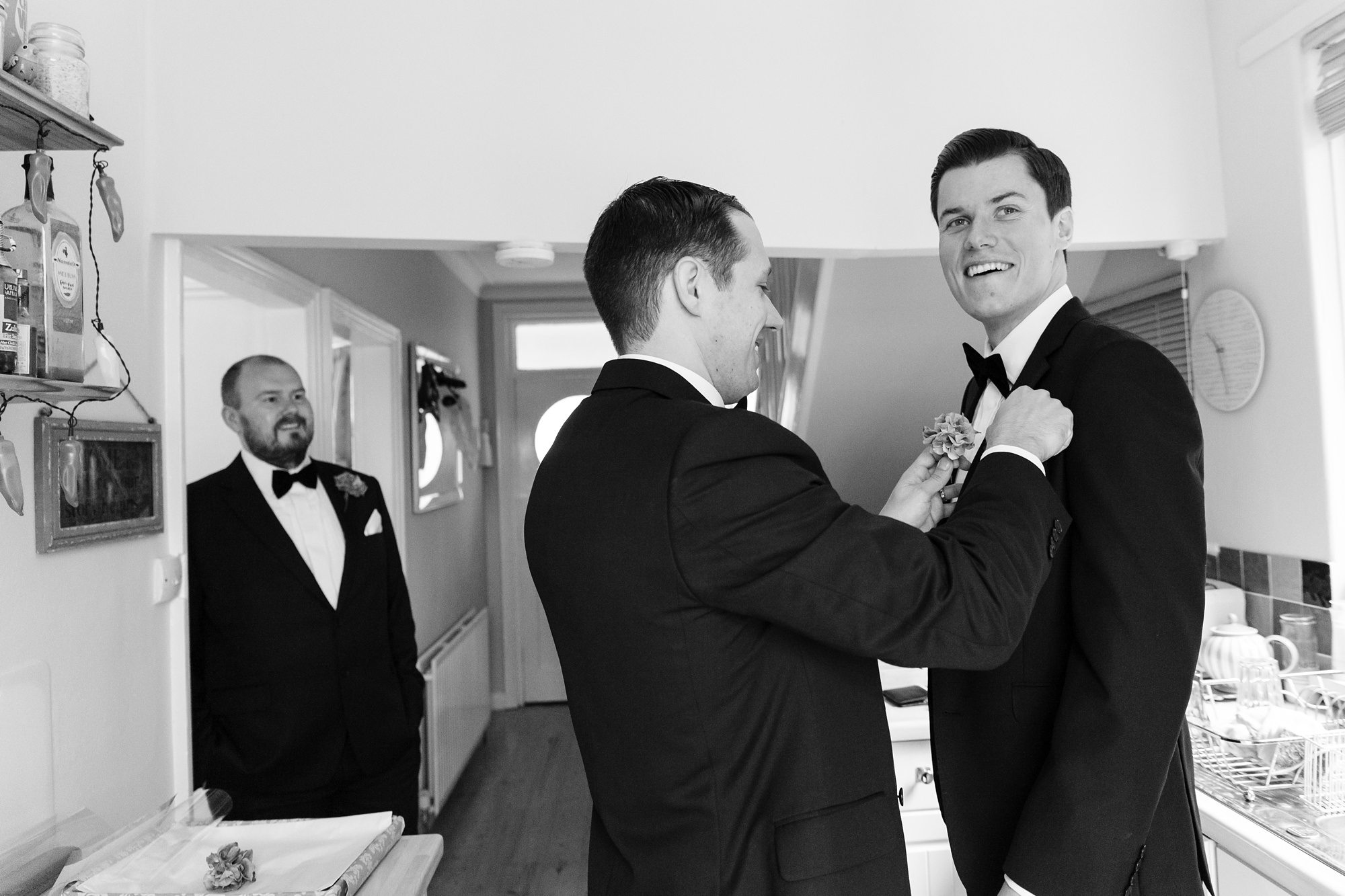 Groom wearing a tuxedo with best man putting on a buttonhole
