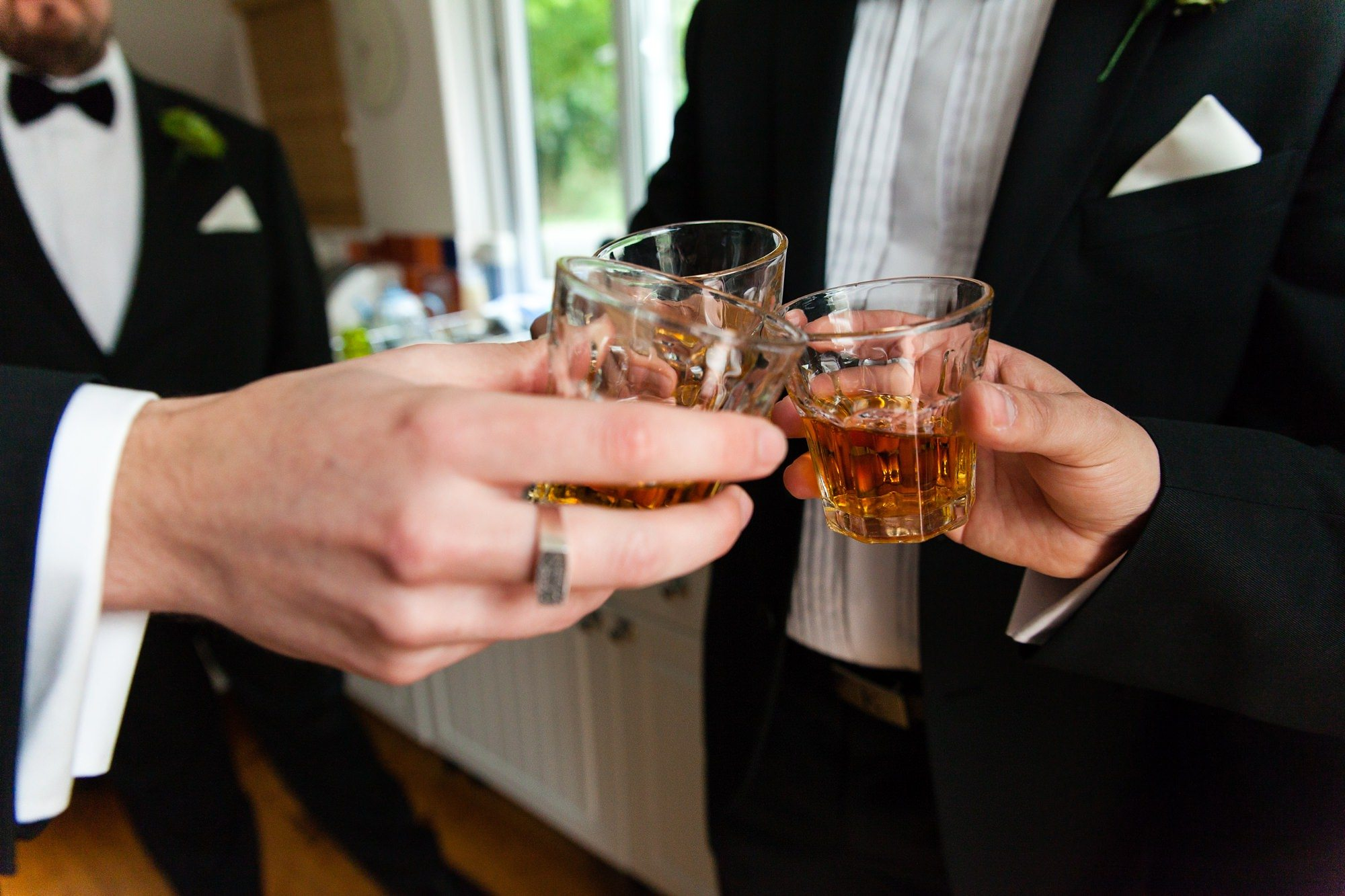 Groom has shots of whiskey in highball glasses before wedding