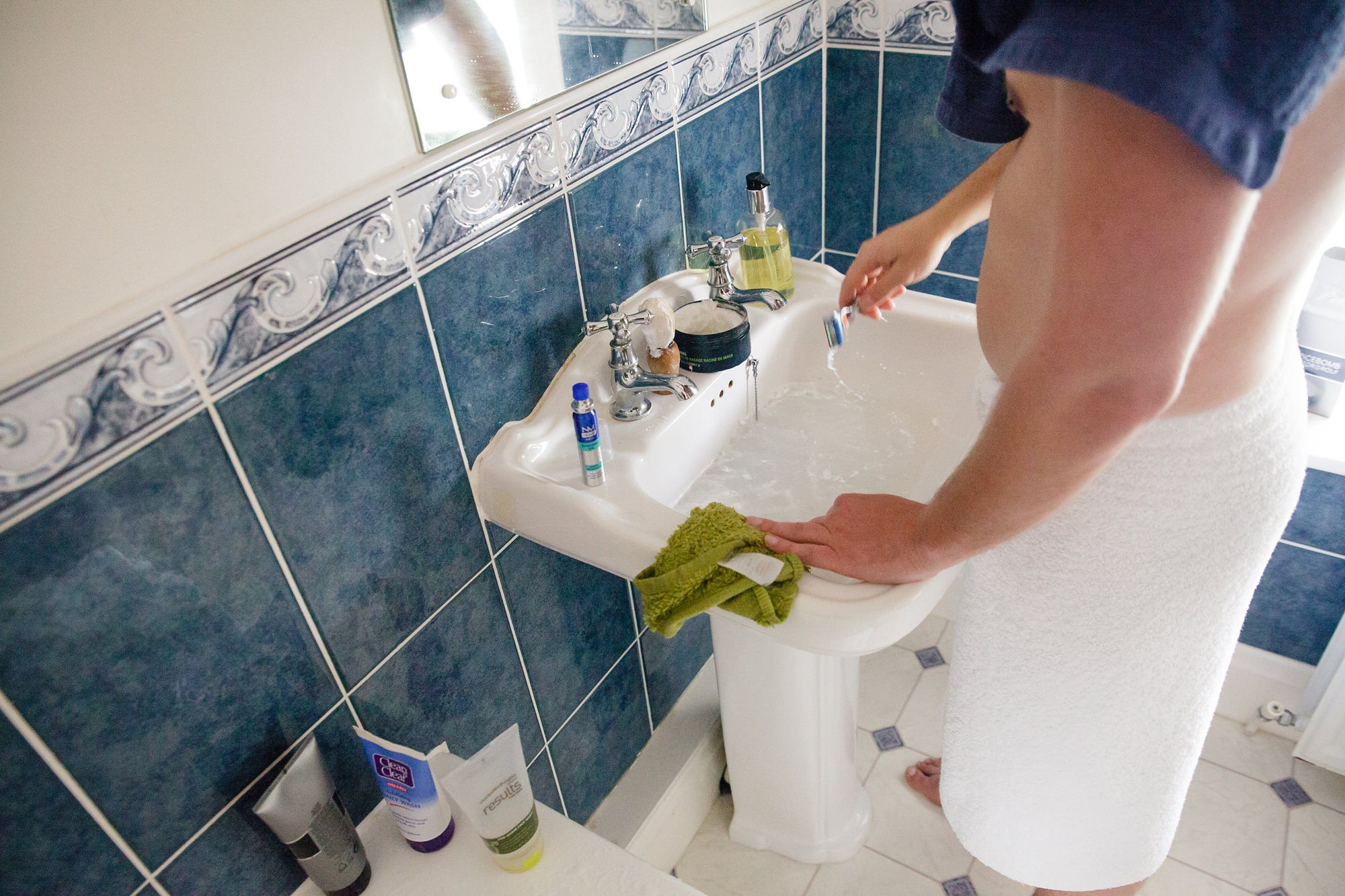Groom shaving at sink with towl over his shoulder
