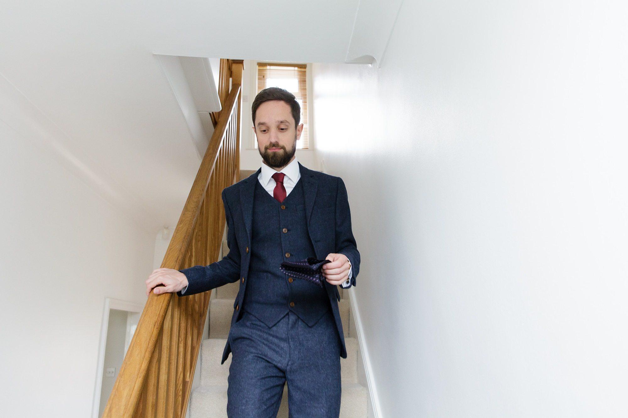 Groom with beard walking down stairs wearing blue suit red tie
