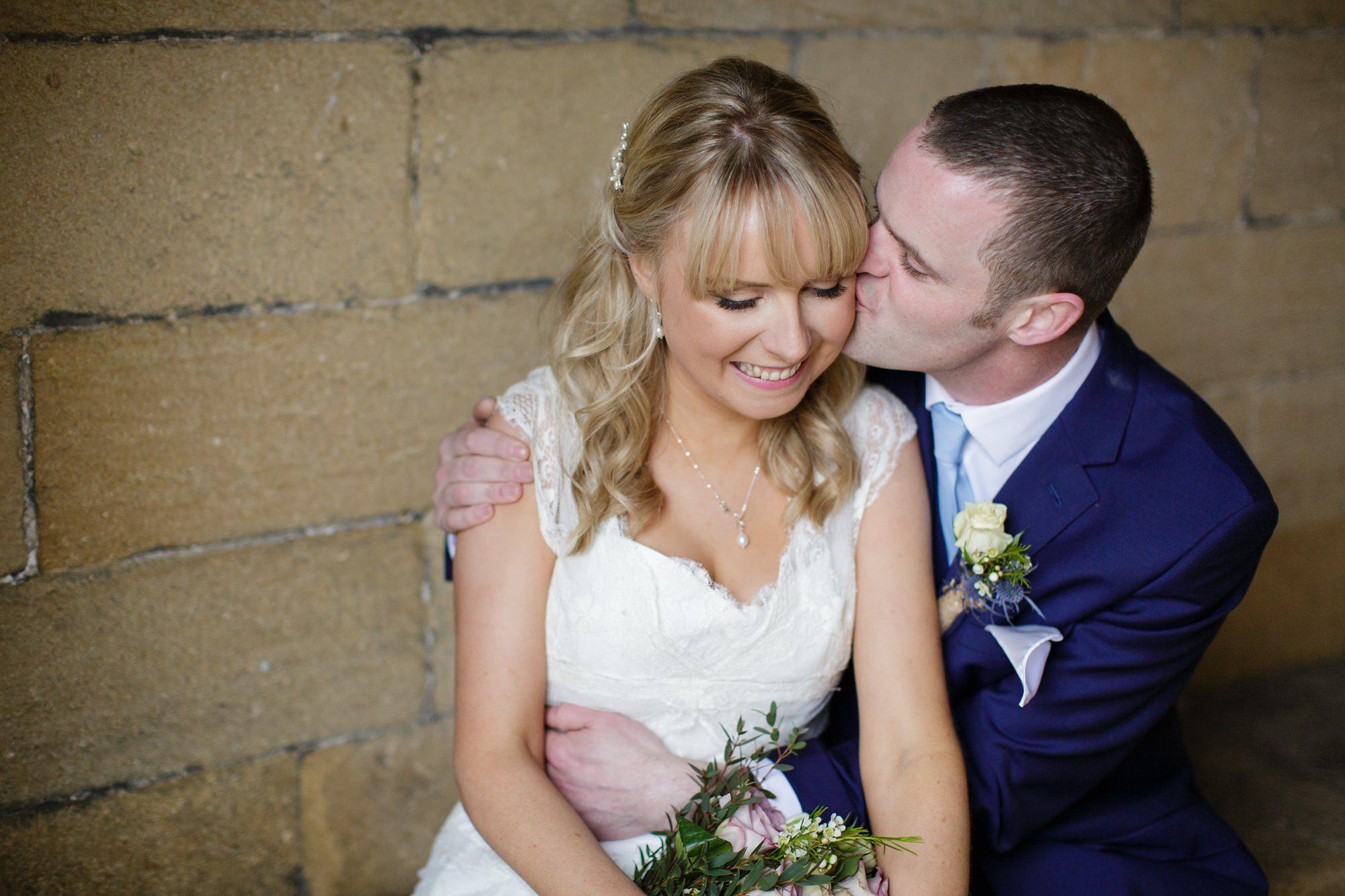 Bride & Groom kissing at cuddling at East Riddlesden Hall Wedding