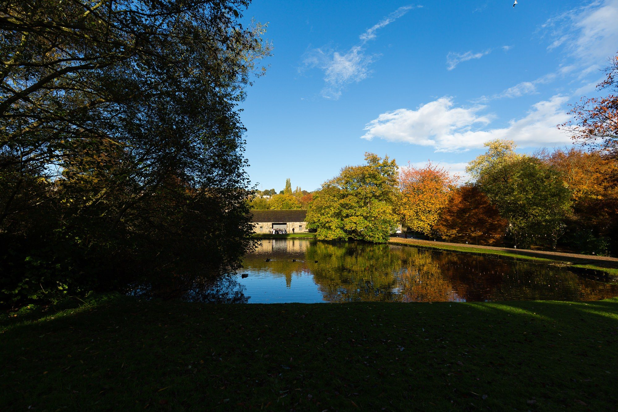 Exterior photograph during autumn at East Riddlesden Hall Airedale Barn by lake with reflections