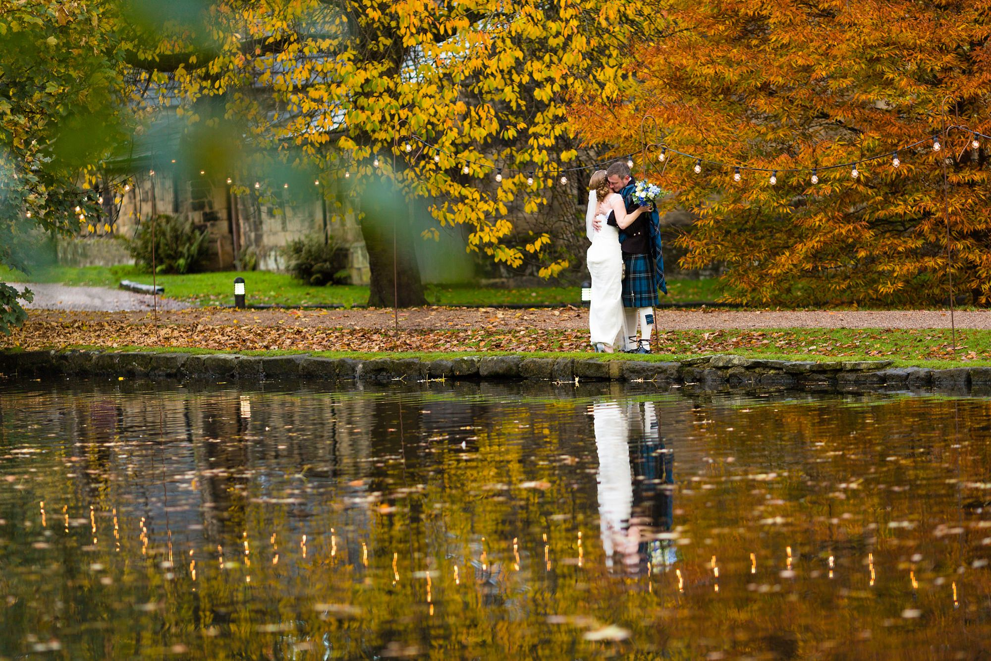 Bride and groom wearing kilt and tartan kiss in autumn colours by lake at East Riddlesden Hall Wedding