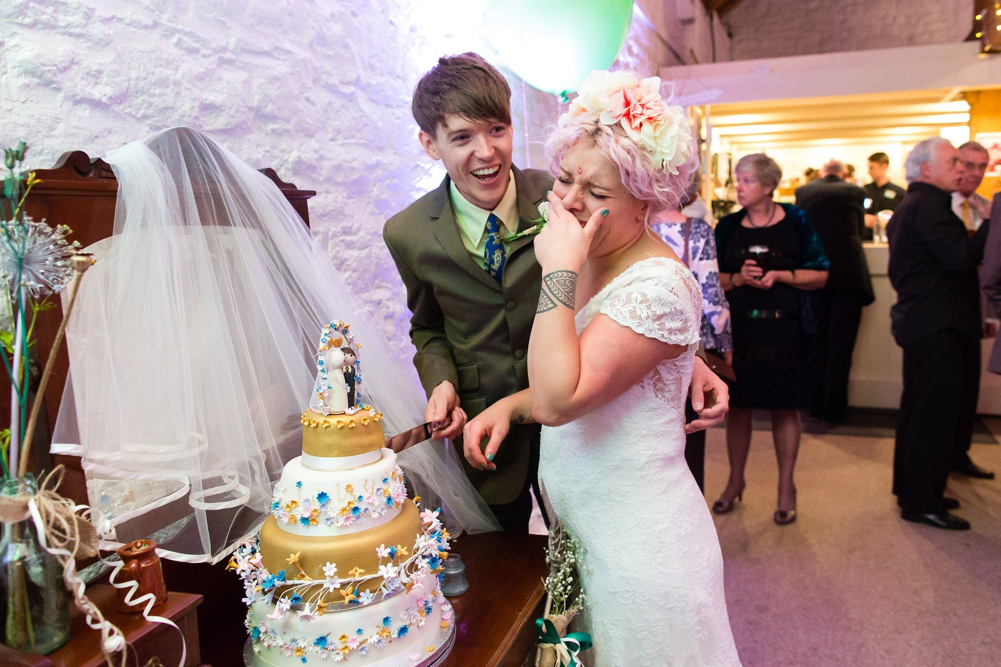 Bride laughing during cake cutting at East Riddlesden Hall