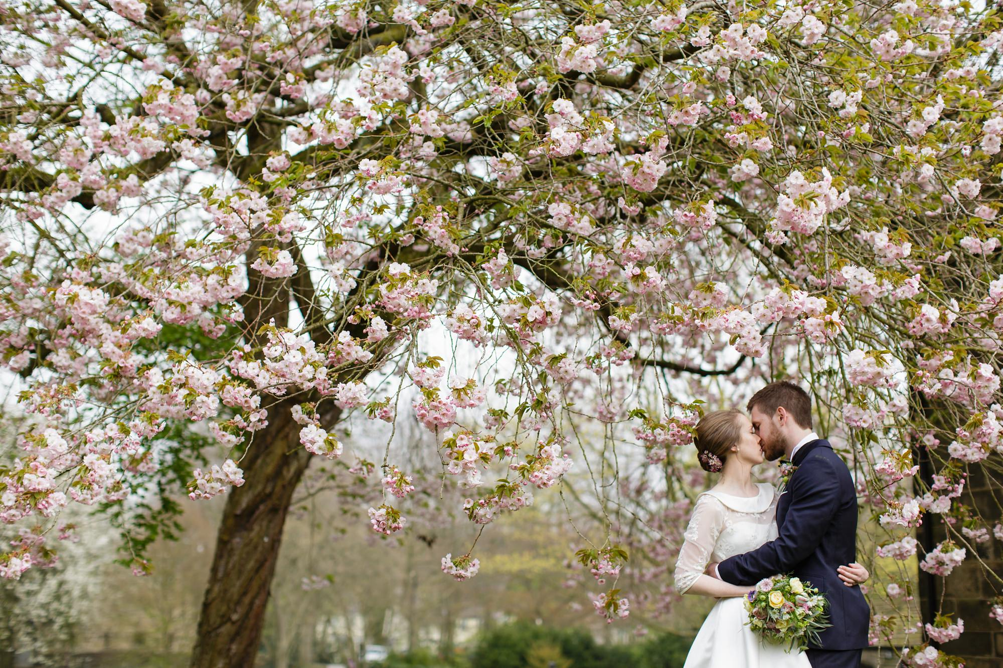 Bride wearing lace wedding dress with peter pan collar at East Riddleden Hall kissing under blossoms
