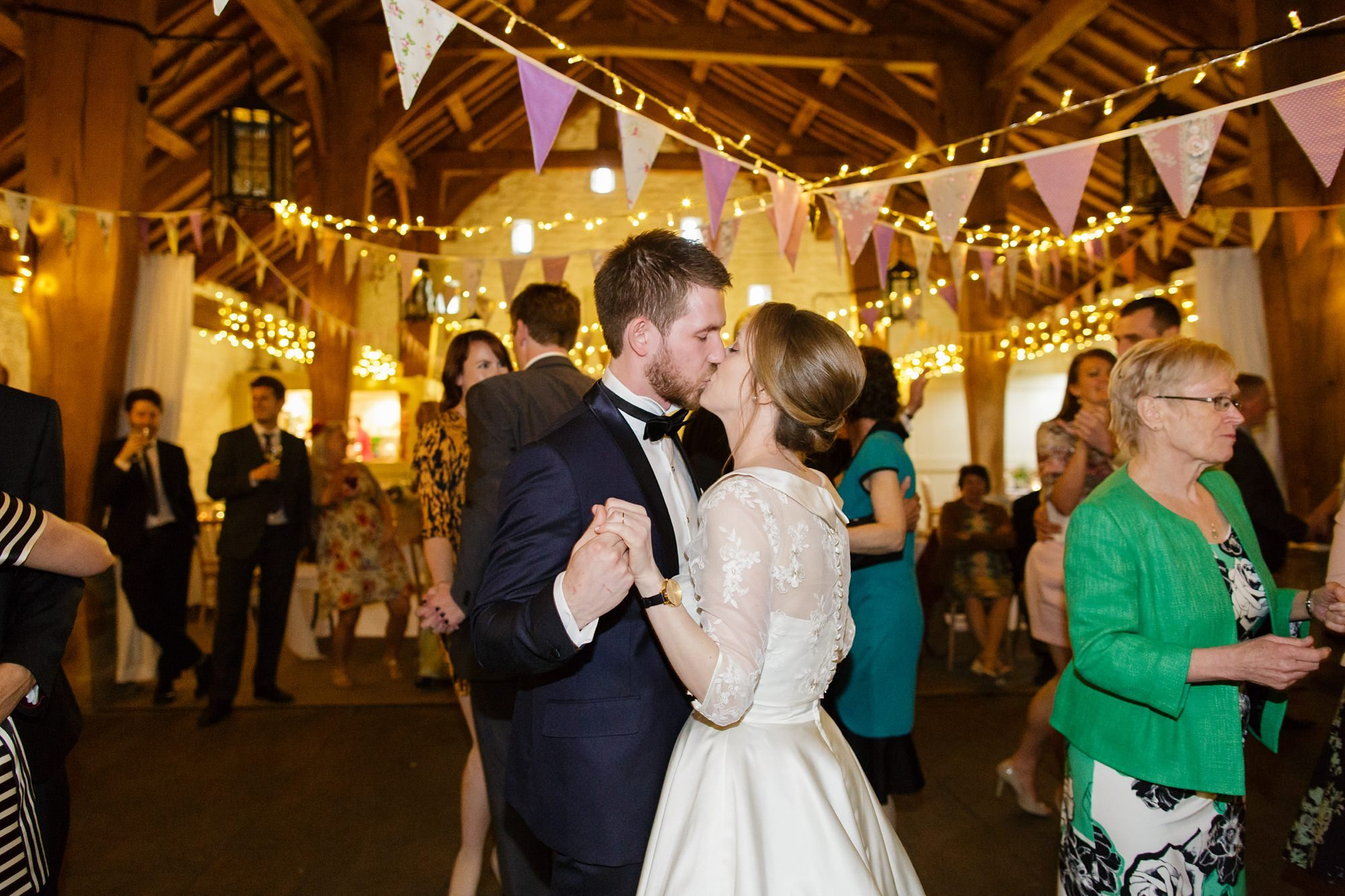 Bride & groom kiss during dance at East Riddlesden Hall with Bunting
