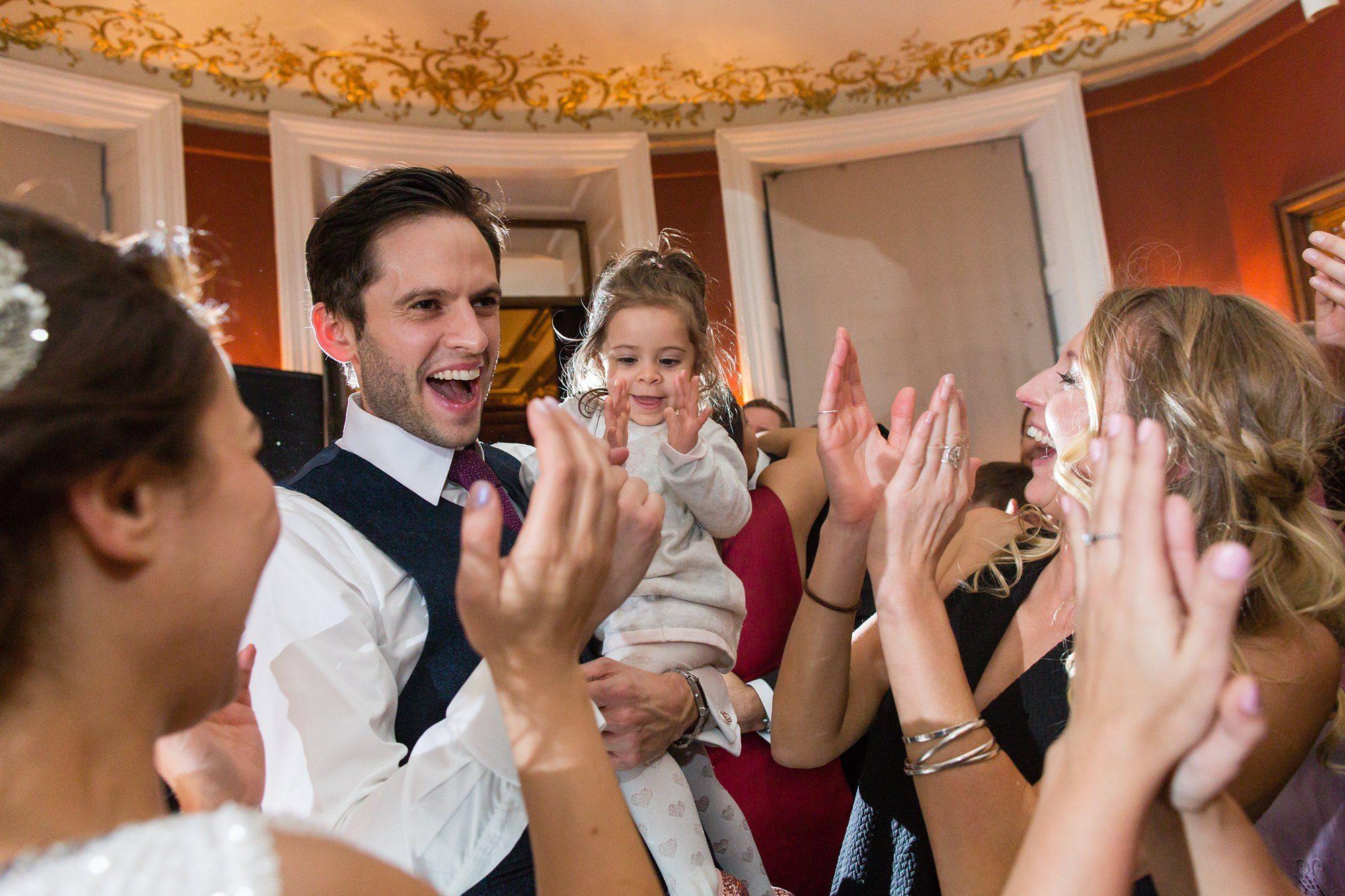 Bride & groom dance with daughter on dance floor Tips for children at weddings