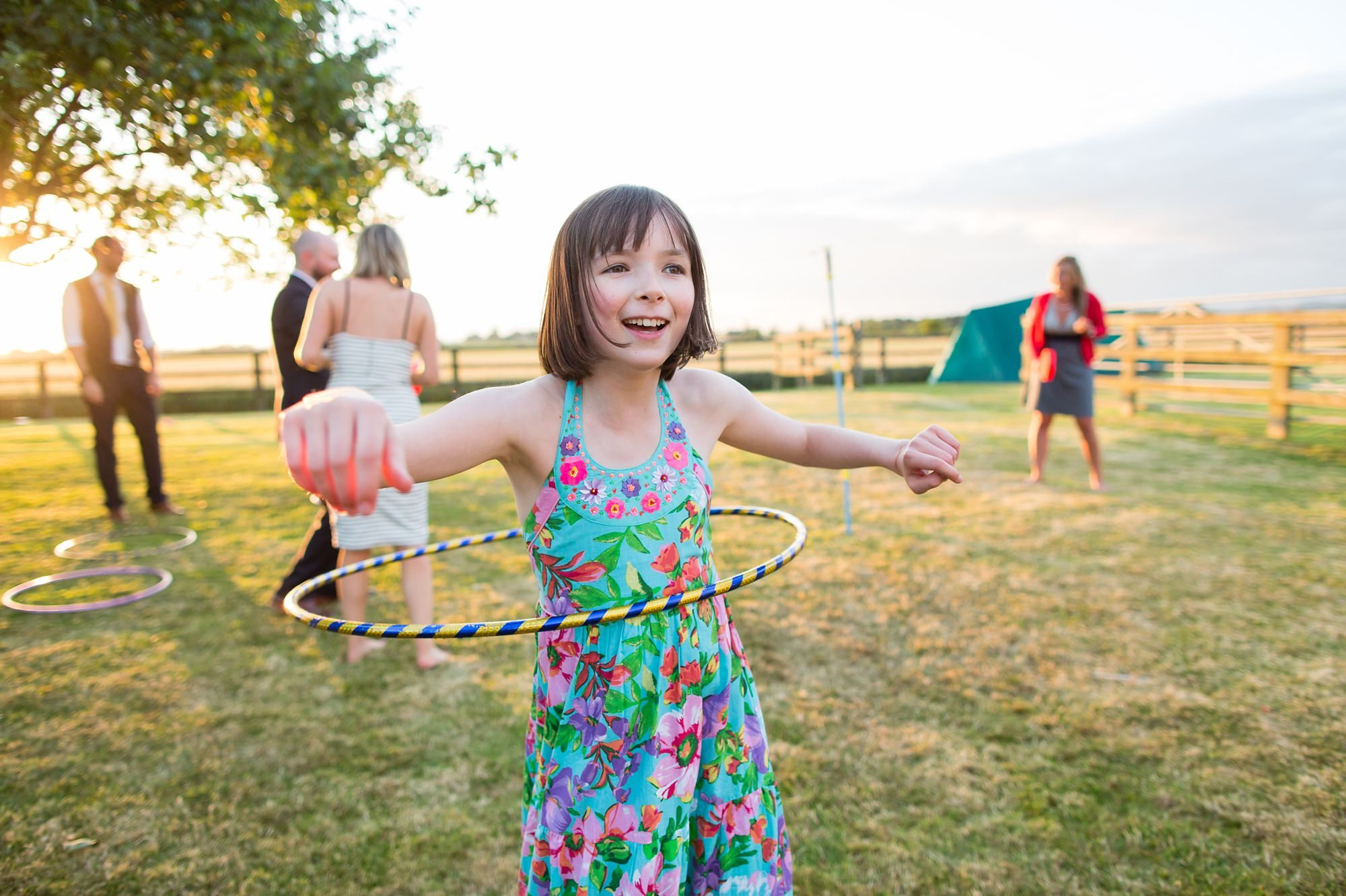 Girl playing hula hoop in sunset Tips for Children at Weddings