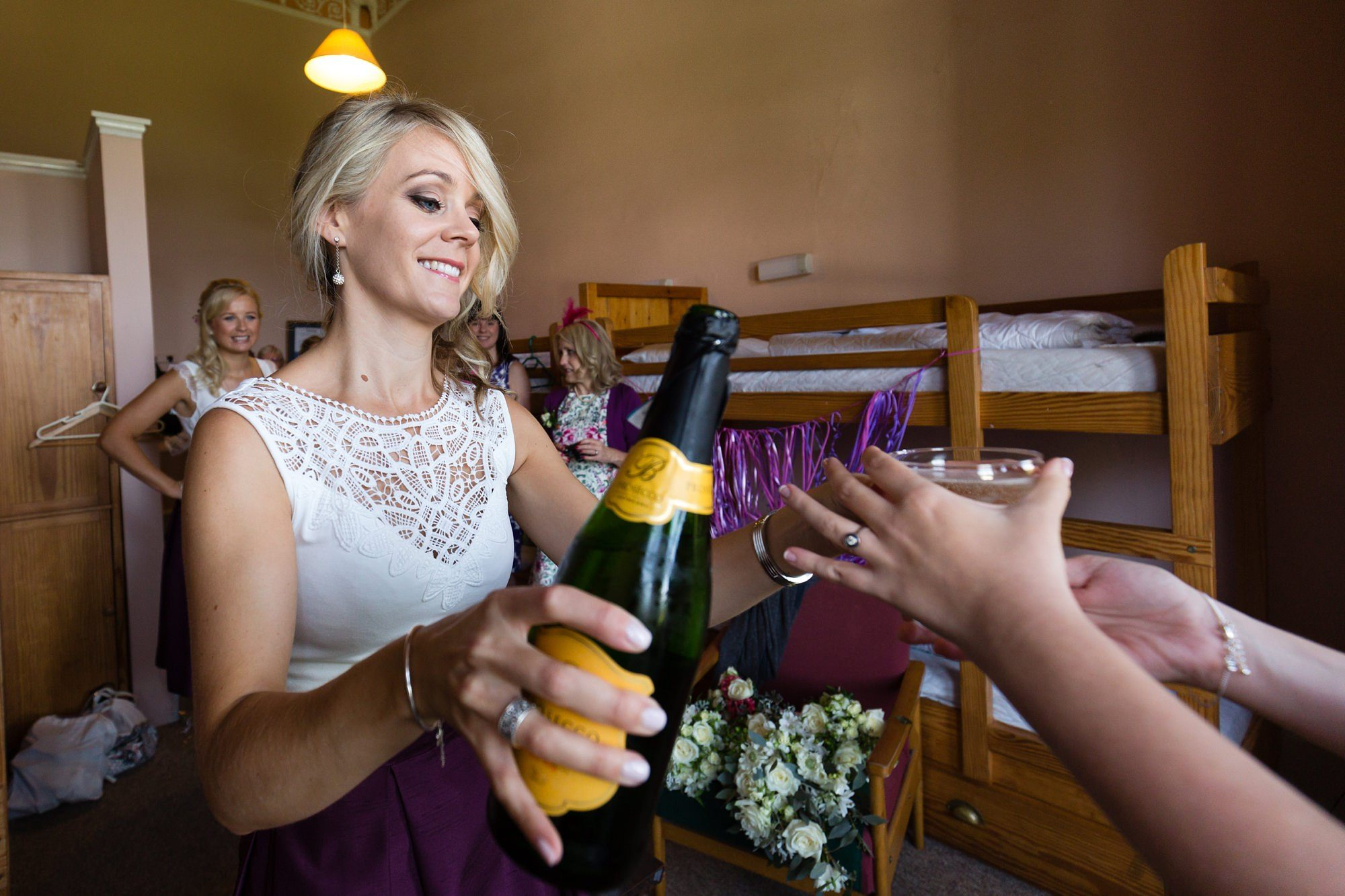 Pouring champagne Derwentwater Independent Hostel Wedding